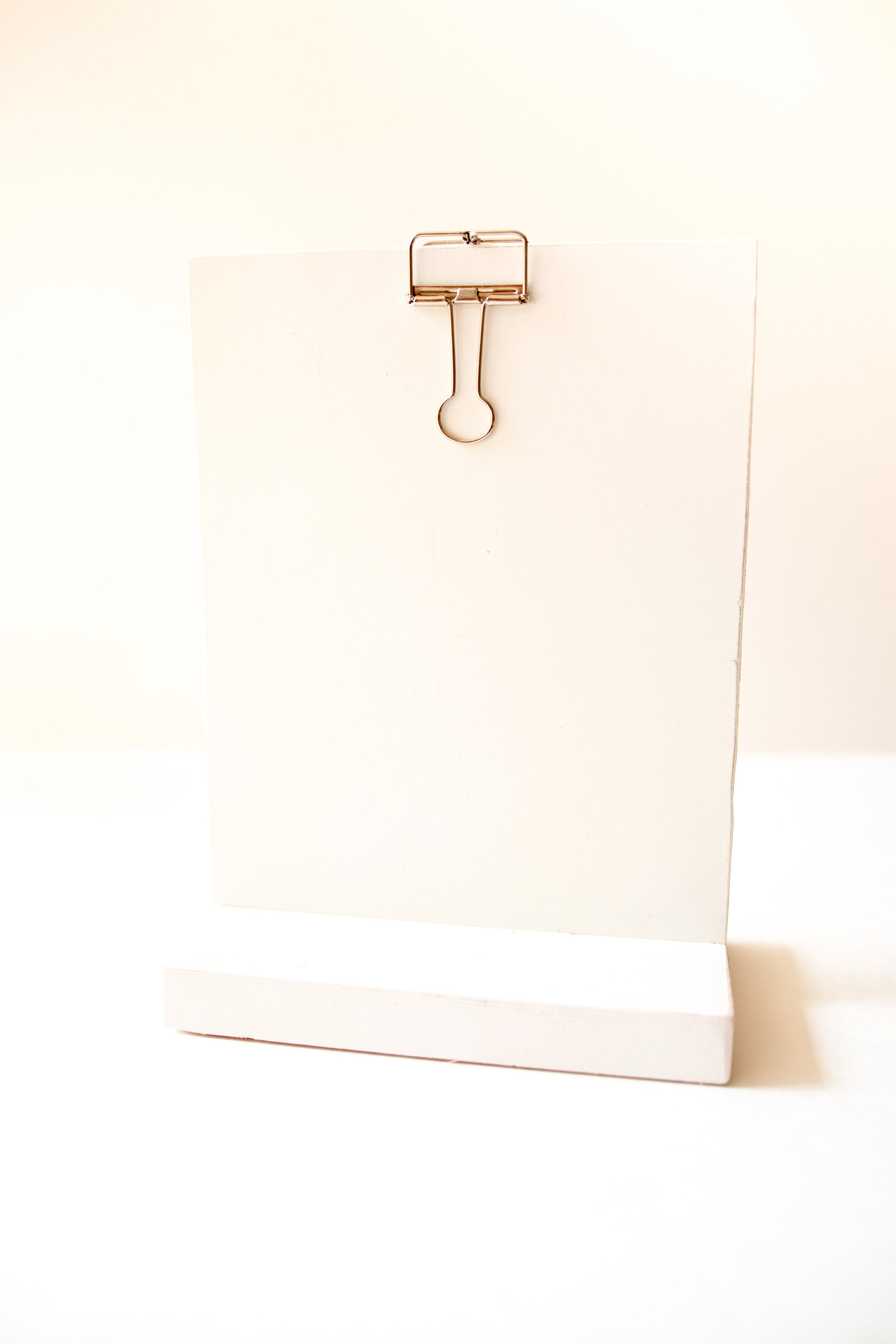 White self standing small clip board for signage at wedding or events through Hue + FA Rentals