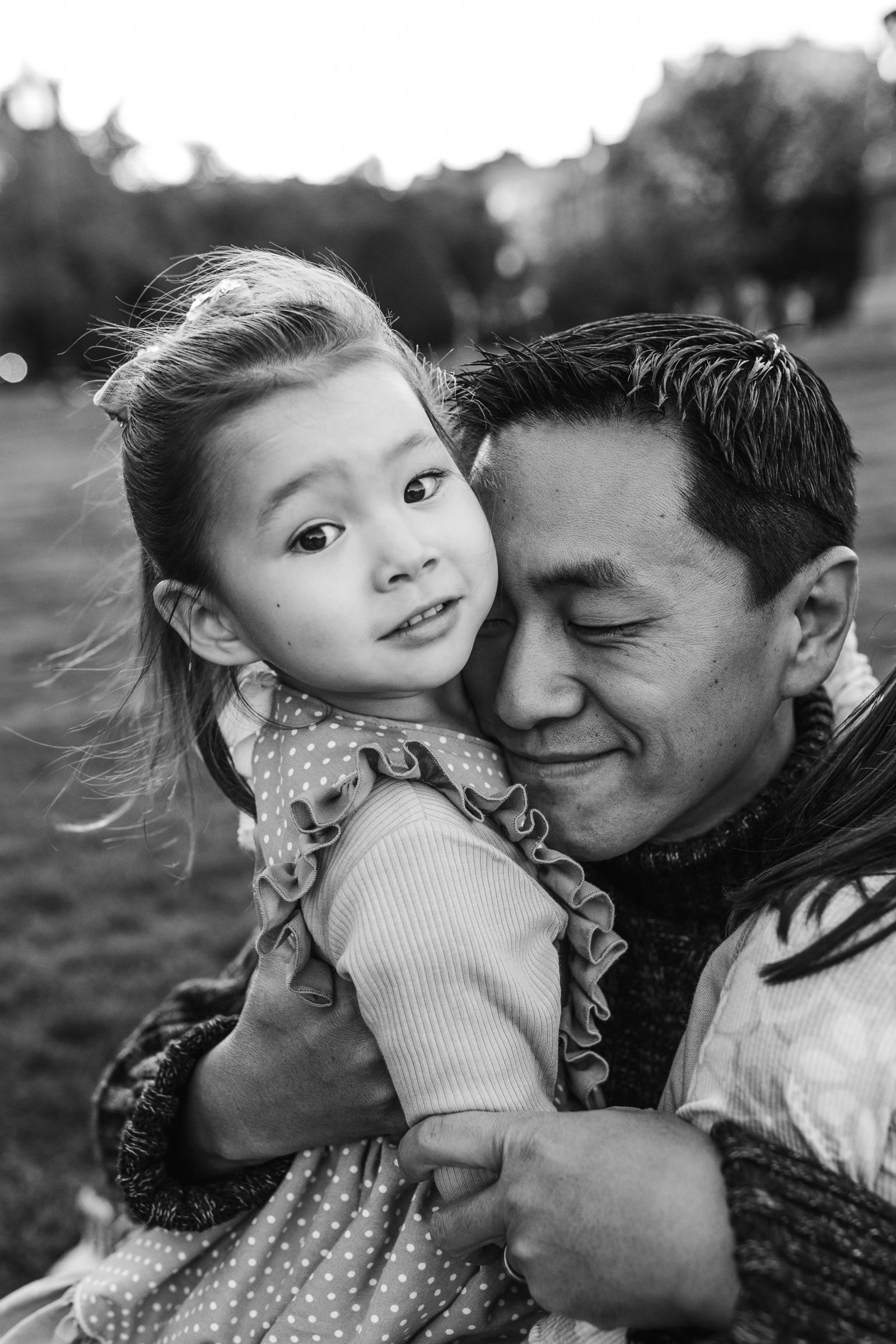 black and white portrait of father snuggling daughter who stares at camera in boston public garden