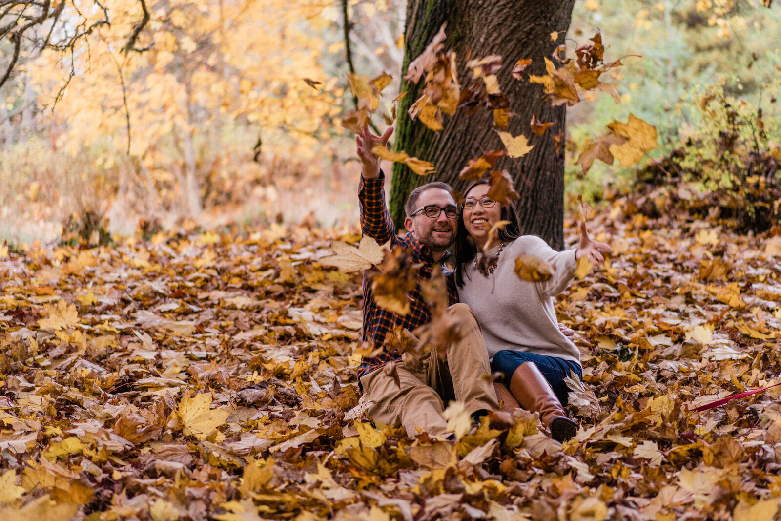 Bride and groom toss fall leaves into the air at best spots for engagement photos in Seattle, Discovery Park, in Magnolia