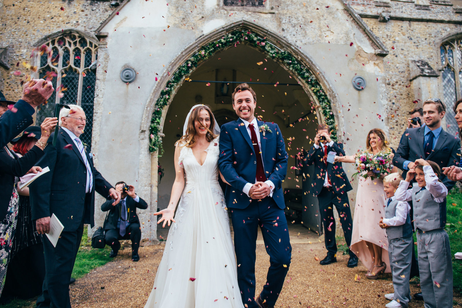 Bride and Groom leaving church down a confetti line after their Suffolk Wedding Ceremony