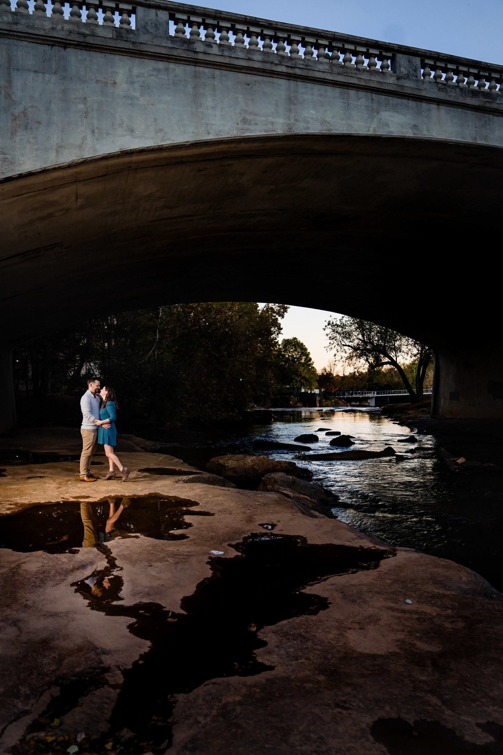 couple standing under bridge by river