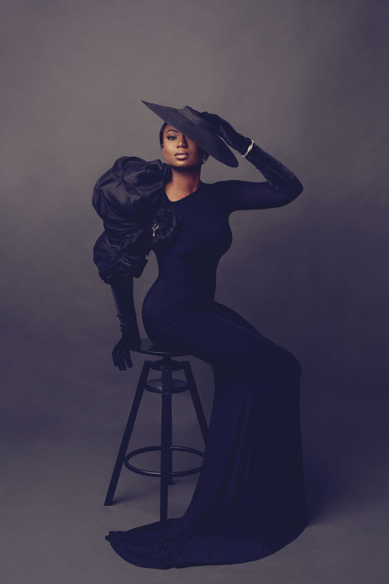 Luxury portrait of a woman in a black gown, sitting on a black stool, looking camera center. Houston, TX.