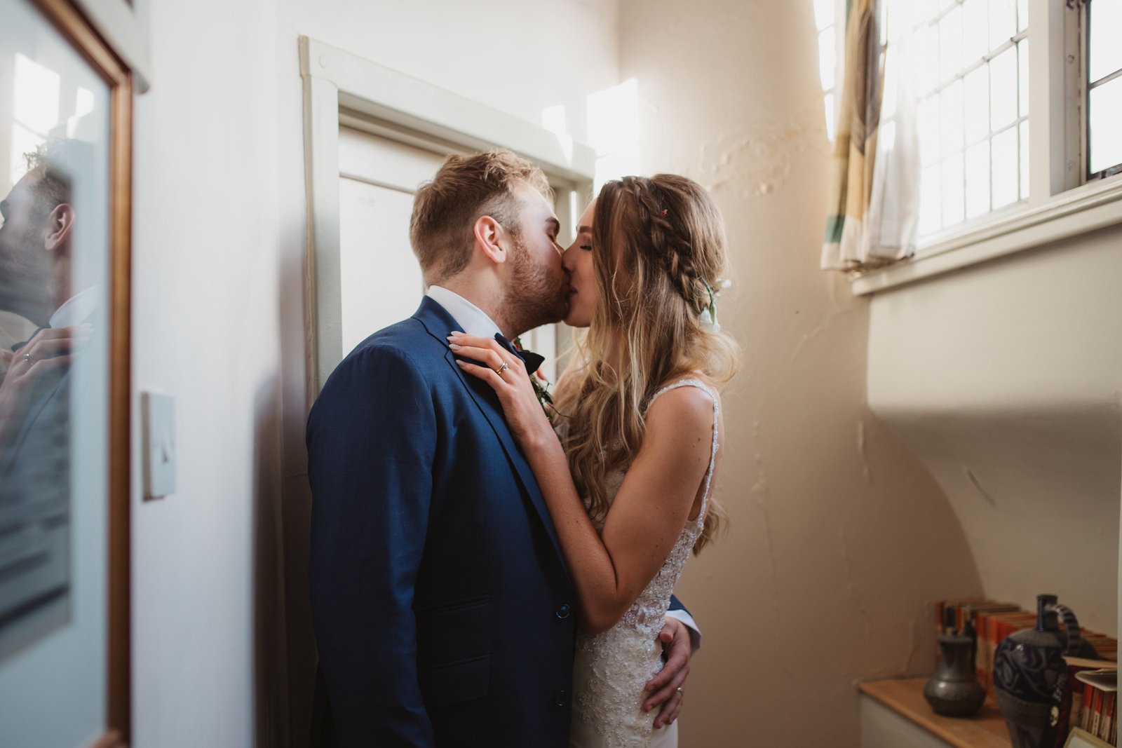 Candid photograph of a Bride and Groom romantically kiss down a corridor during their wedding reception
