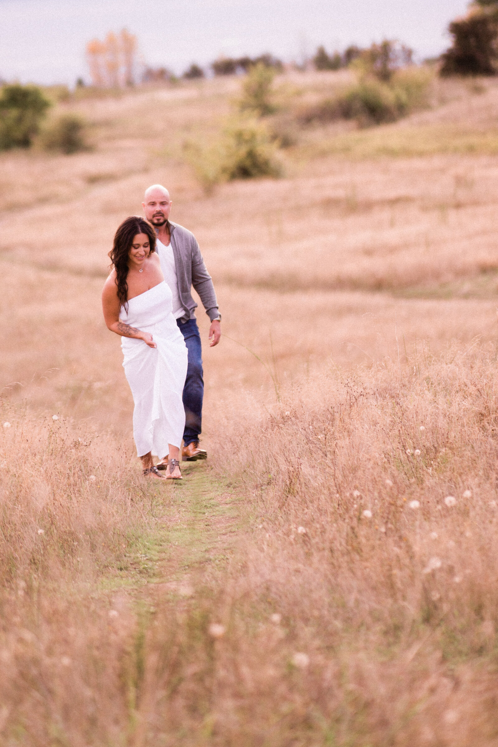 Husband and wife stroll through flowers and tall grasses at the best spot for intimate engagement photos in Seattle