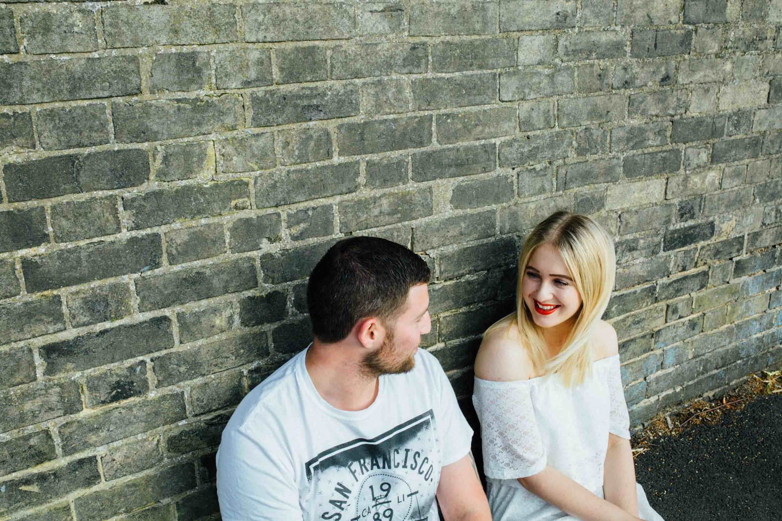 Happy engaged couple lean against grey brick wall for a natural couples photo