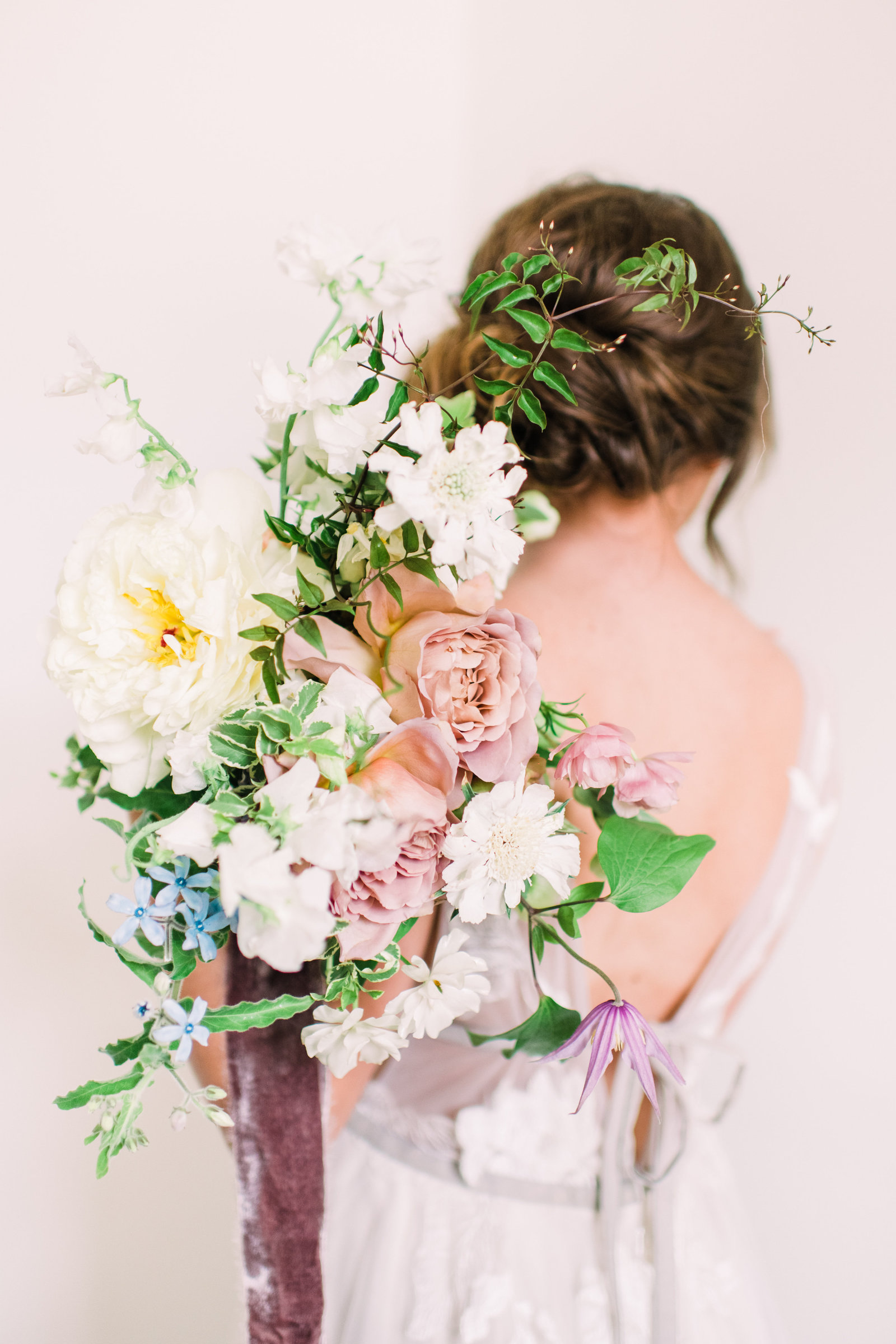 organic wedding bouquet over bride's shoulder