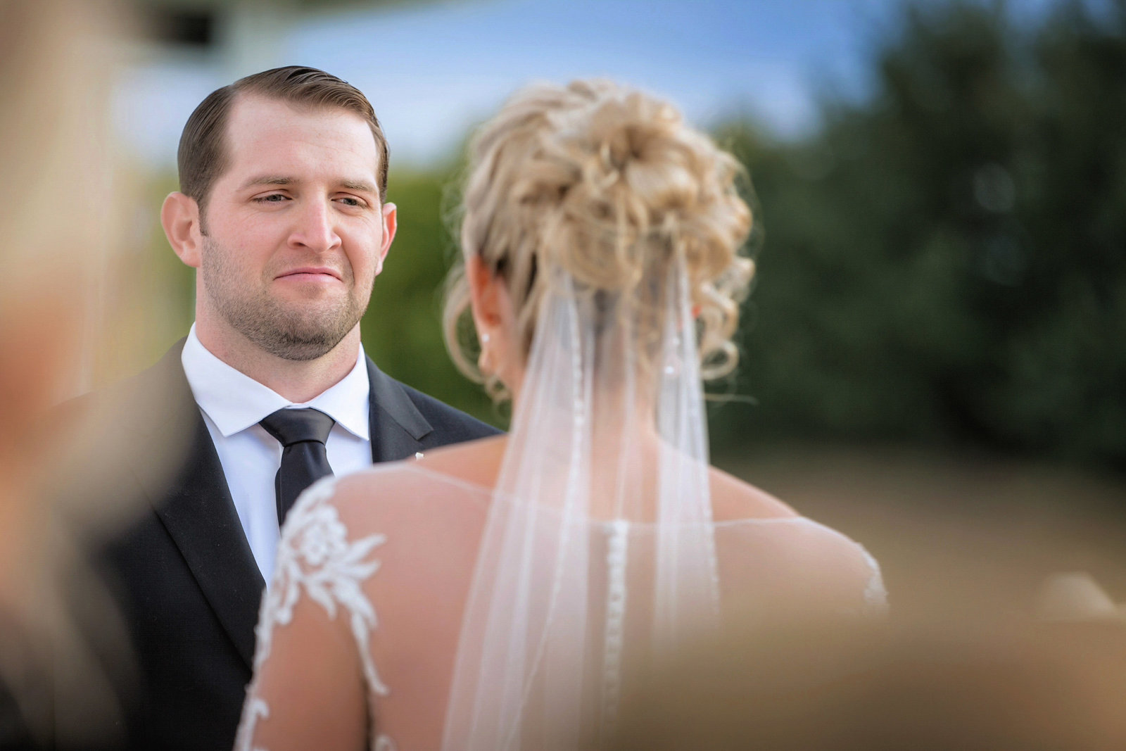 Groom looking into brides eyes during ceremony