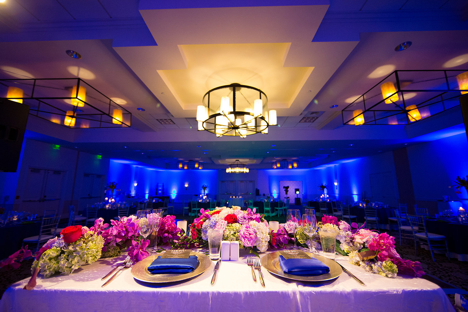 Indian weding reception head table with beautiful flowers and dramatic uplighting