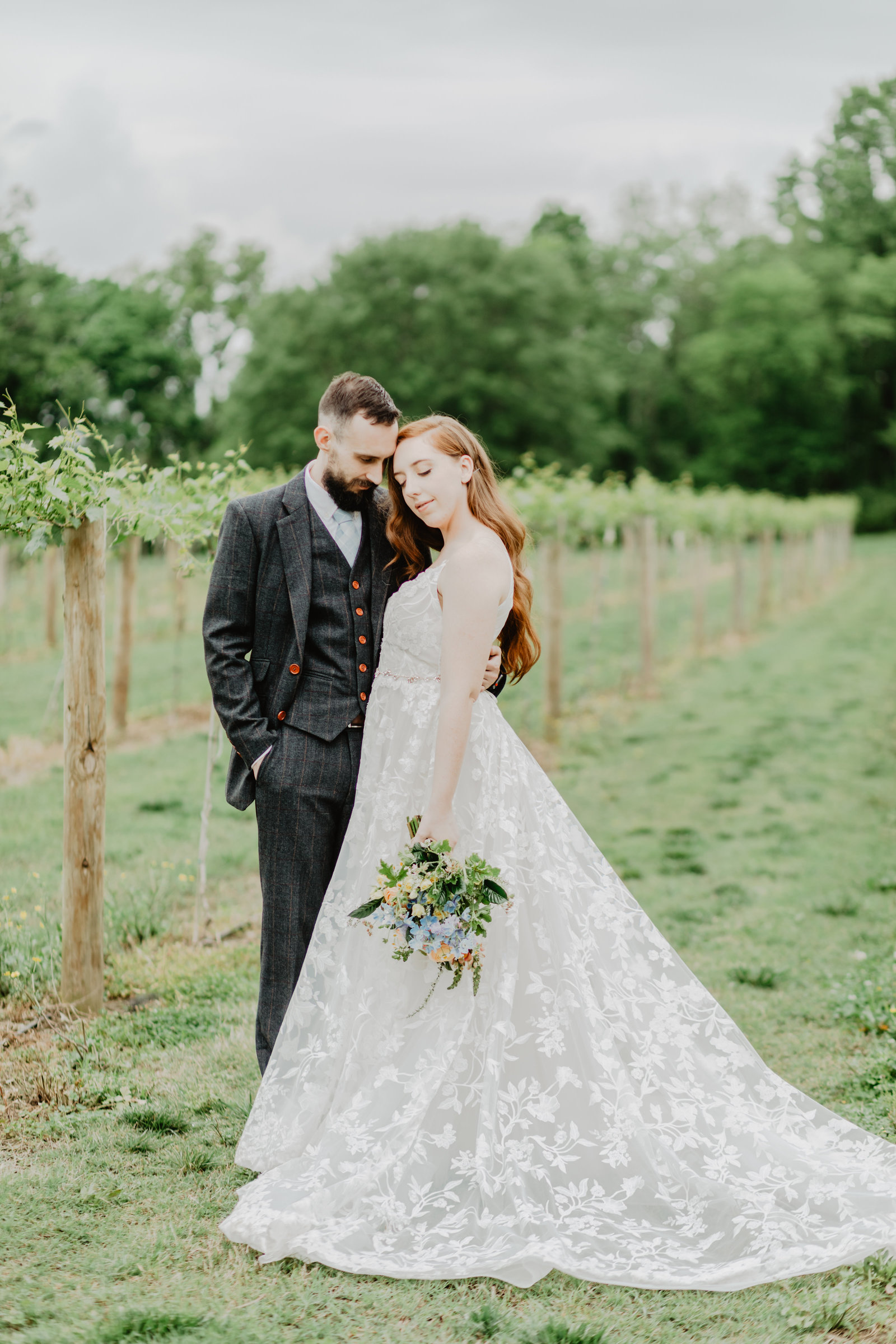 Bride and Groom stand in vineyard cuddling at Long Hollow Gardens