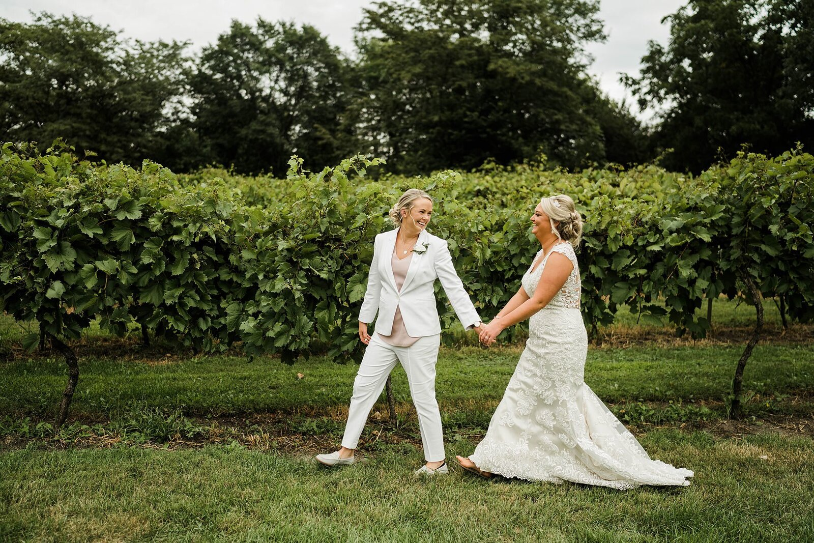 two brides hold hands walking through vineyard at the chateau