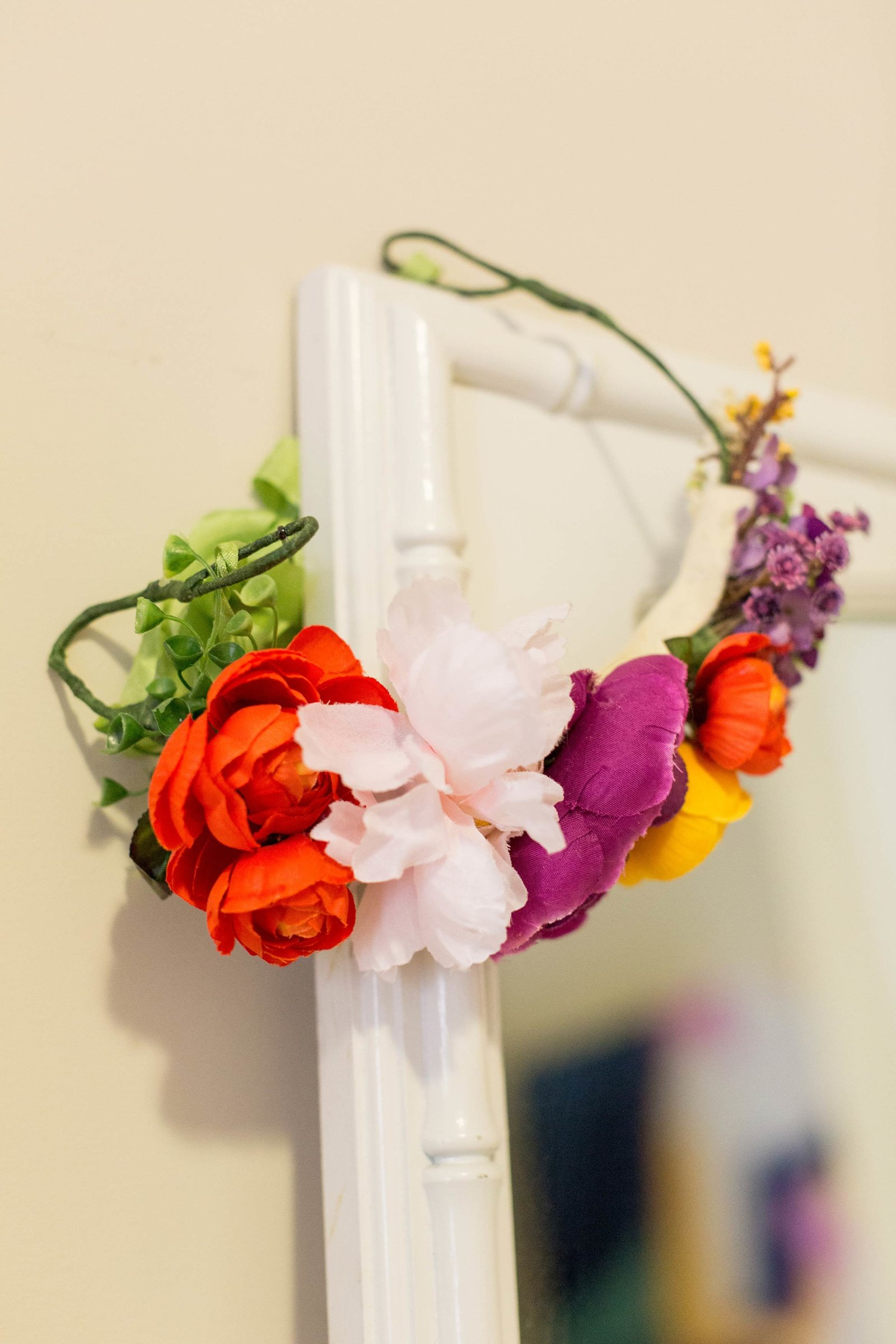 A bright flower crown hangs on the corner of a mirror.