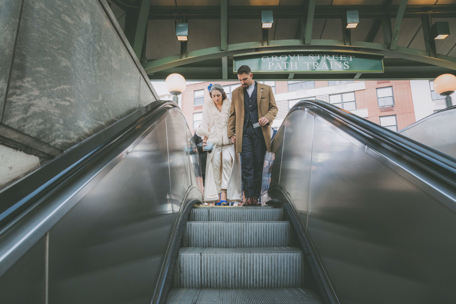 Bride and groom goes down a subway escalator during their elopement in Jersey City.