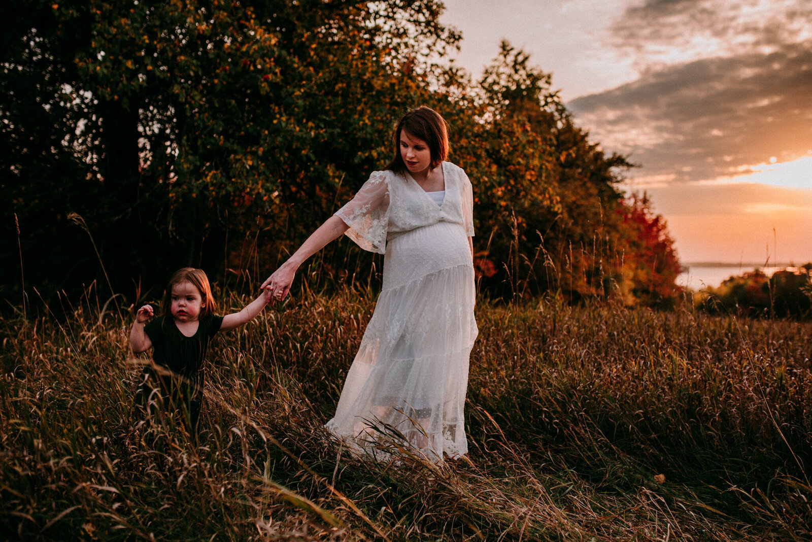 Pregnant mother leading her daughter at sunset in Kawartha Lakes