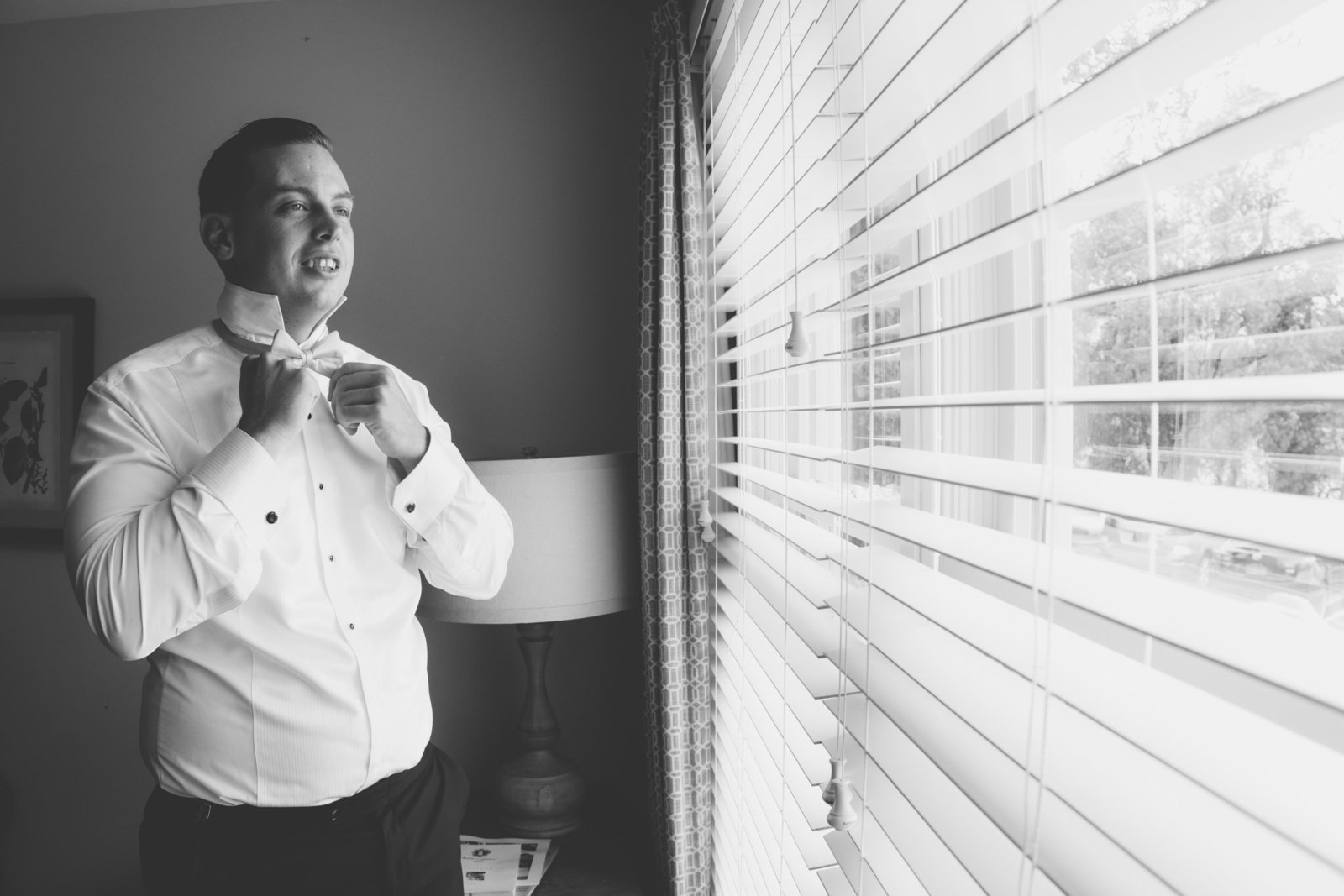 black and white photo of groom looking out the window at Three Village Inn