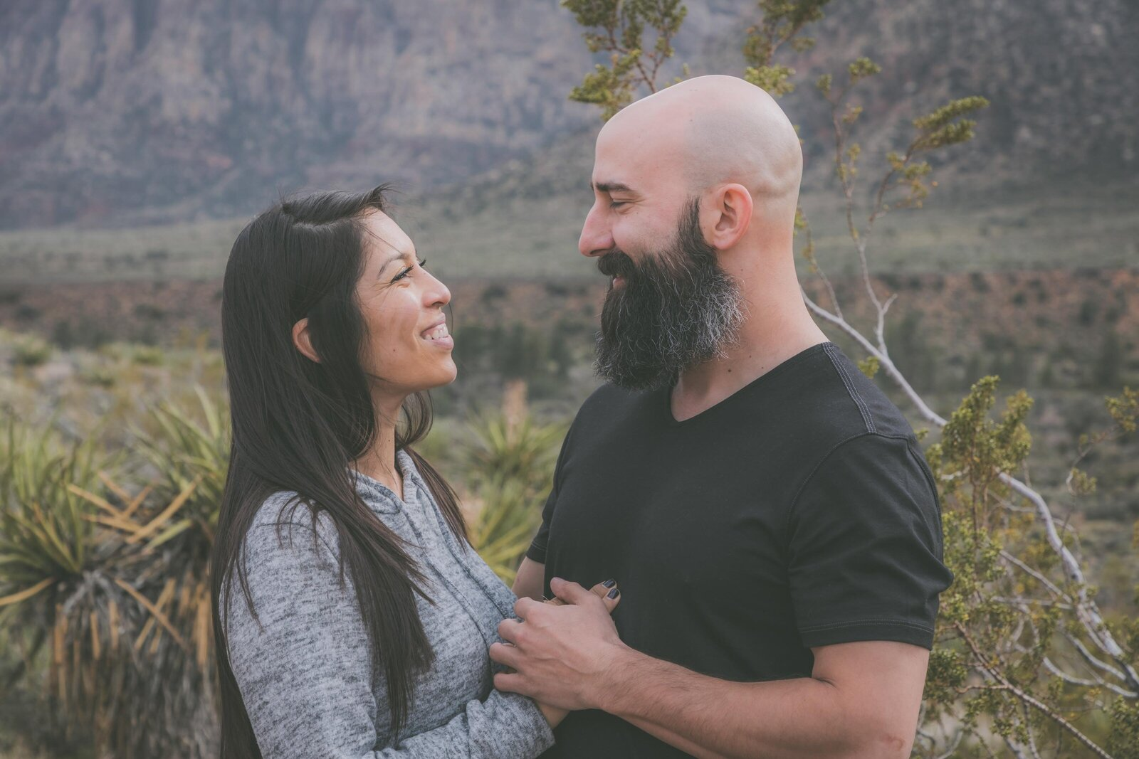 Woman and man hold hands and smile in a desert setting.