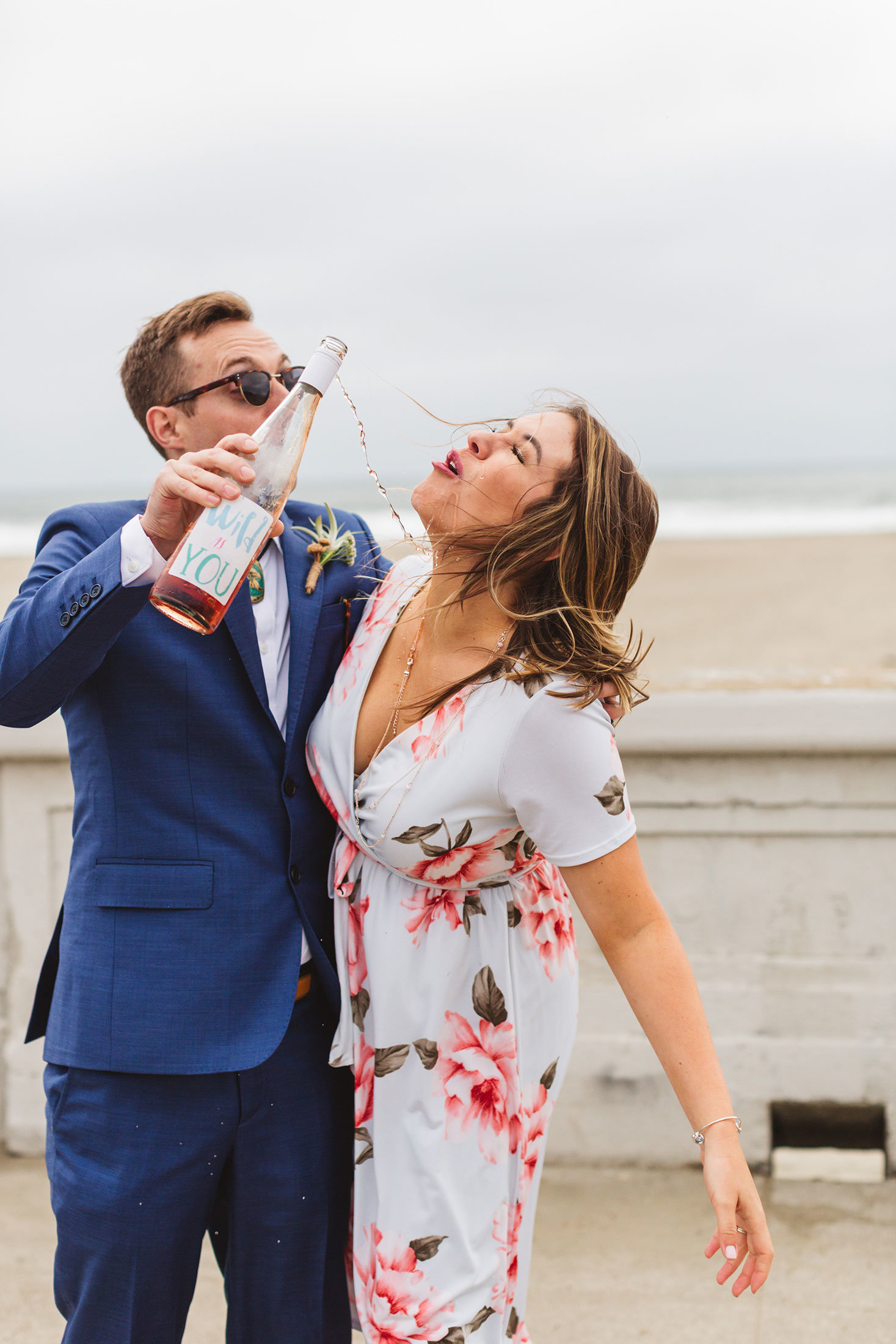 san francisco ocean beach groom pouring rose wine into bridesmaid's mouth
