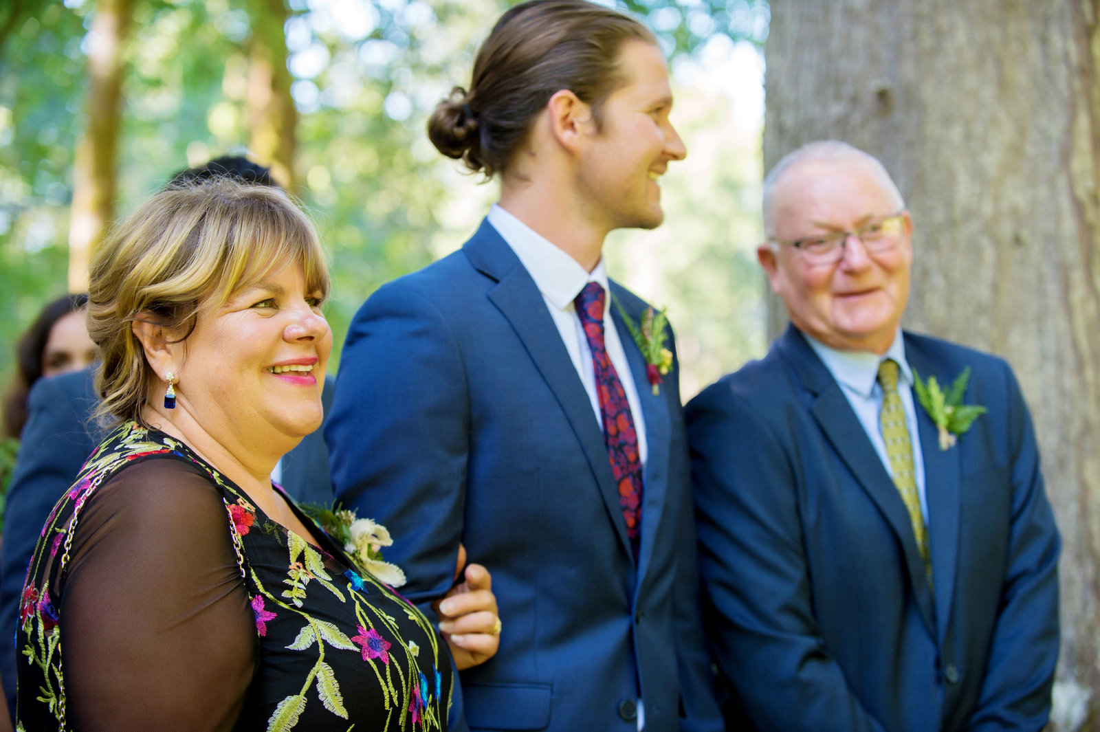 mother and father of groom get ready to walk son down the aisle