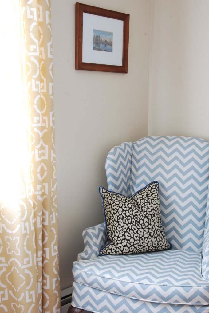 A blue and white chevron chair with a leopard throw pillow.