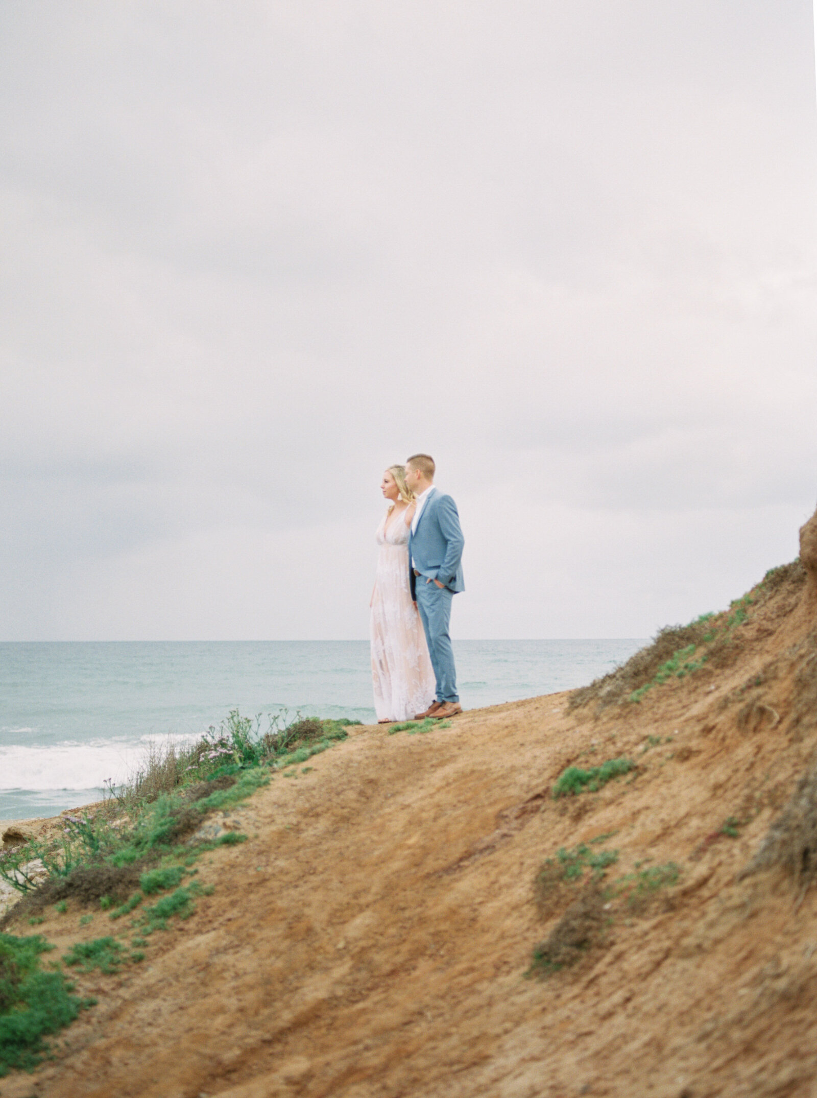Elegant fine art romantic engagement session at the Sunset Cliffs in San Diego with white dress by Liz Andolina Photography