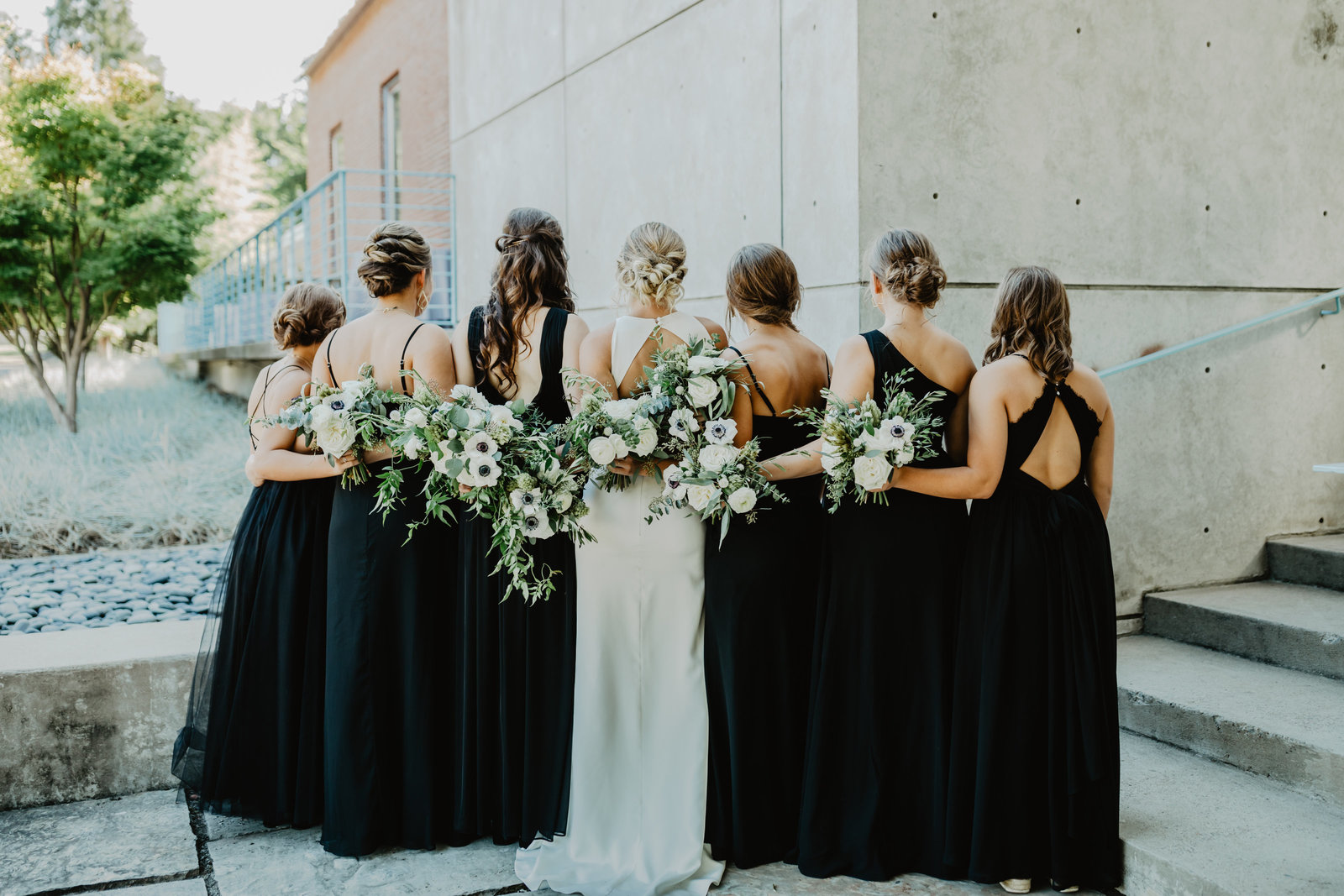 Bridal Party stands facing away with bouquets behind their backs at The Ruby