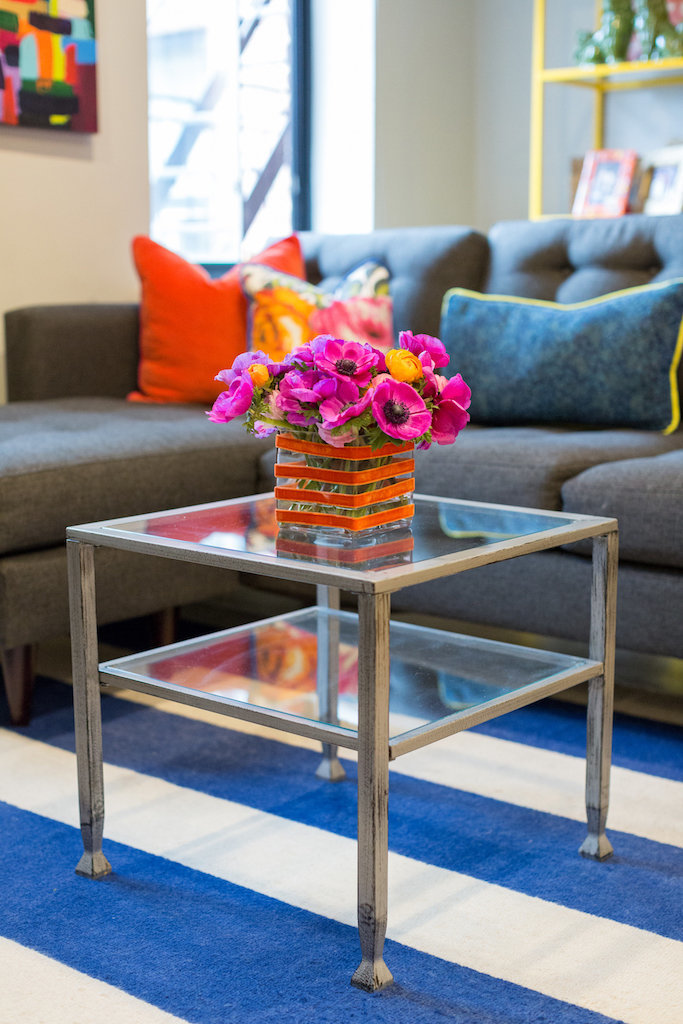 A metal and glass coffee table with an orange vase and pink flowers.