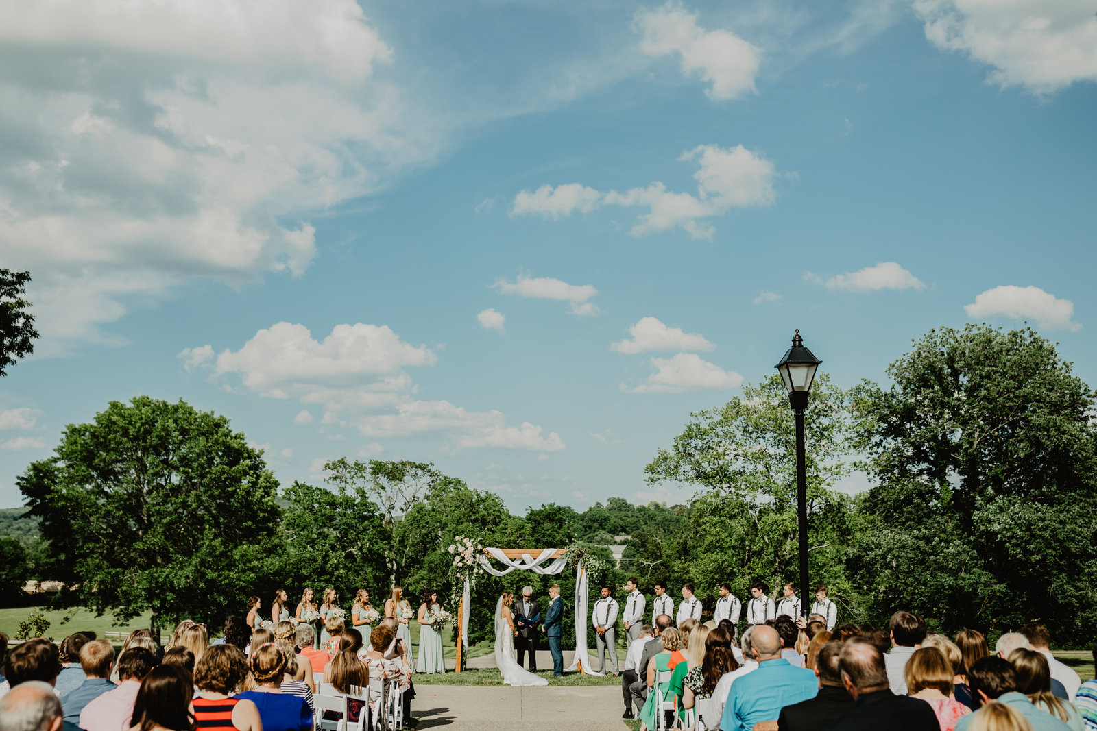 Bride and Groom standing in front of all their guest getting married at Ravenswood Mansion