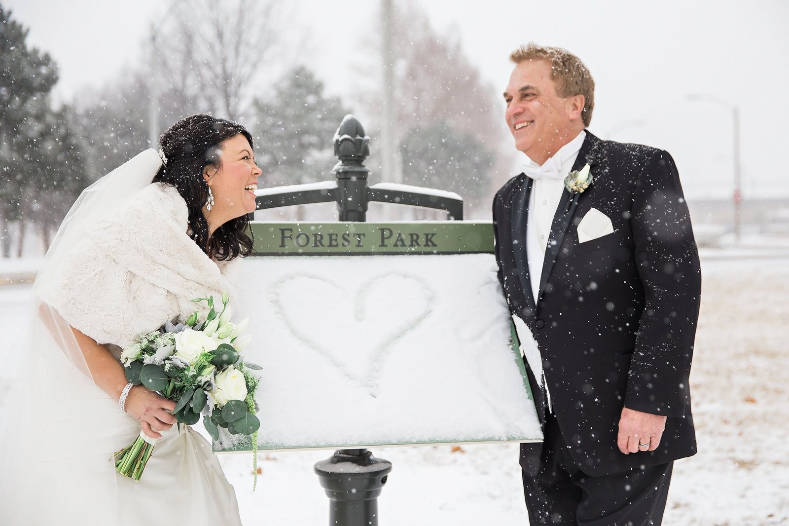 Couple having fun at their snowy Forest Park wedding in St Louis
