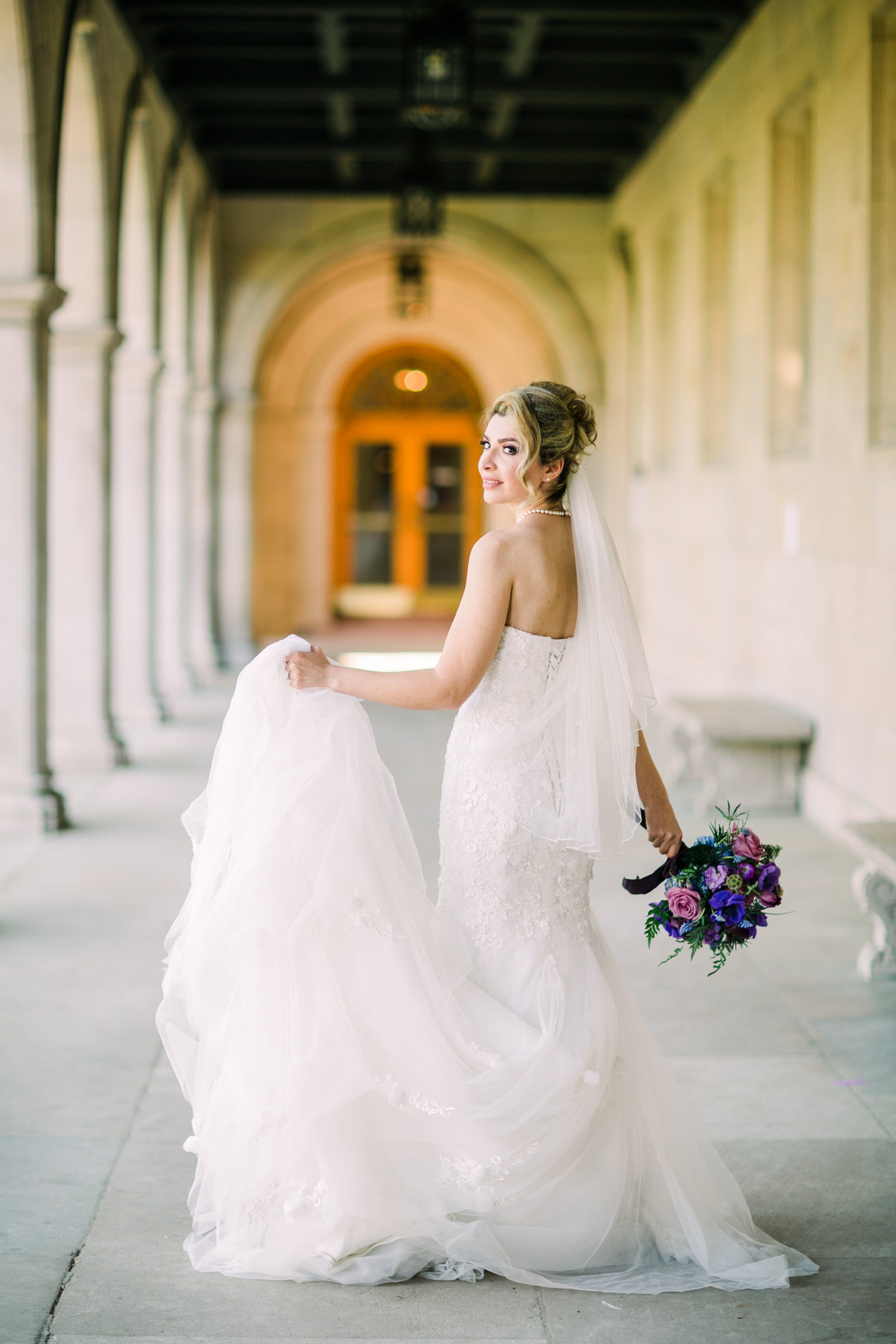 Bride, Zohra, walks away wedding dress train in hand down a hall of Washington University.