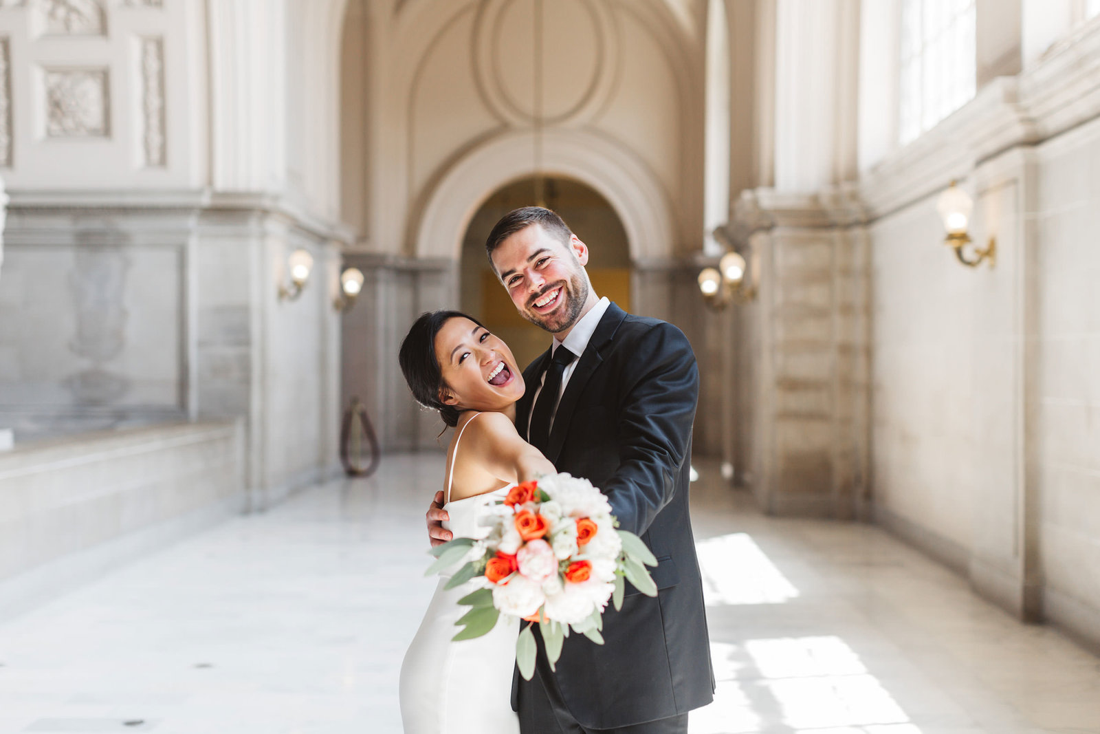 happy joyful newlywed couple dancing after their San Francisco City Hall on 4th floor