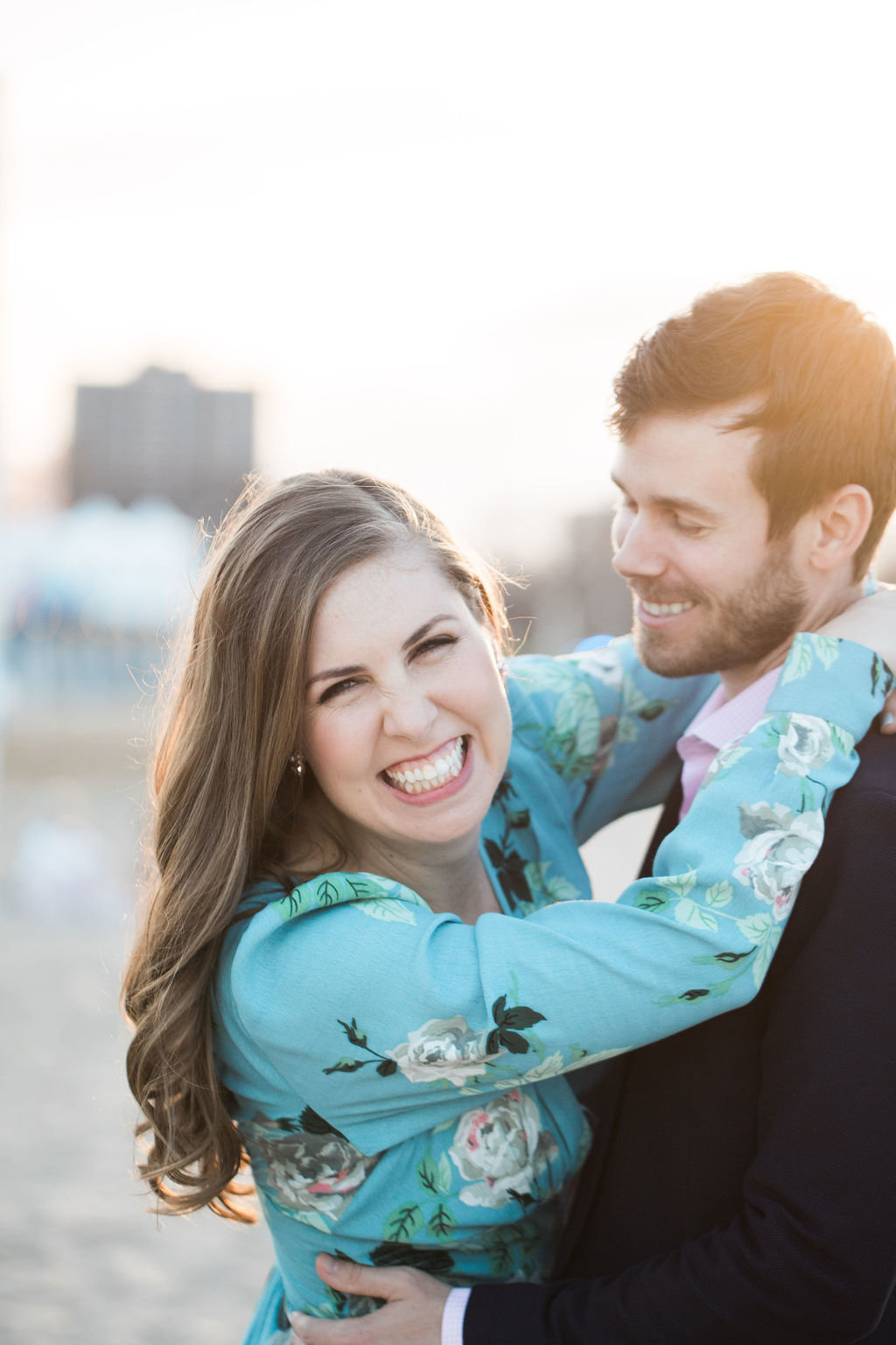 Bride with arms around groom in engagement portrait
