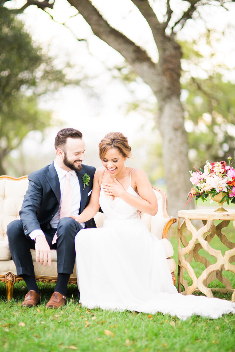 bride and groom seated while laughing together outside