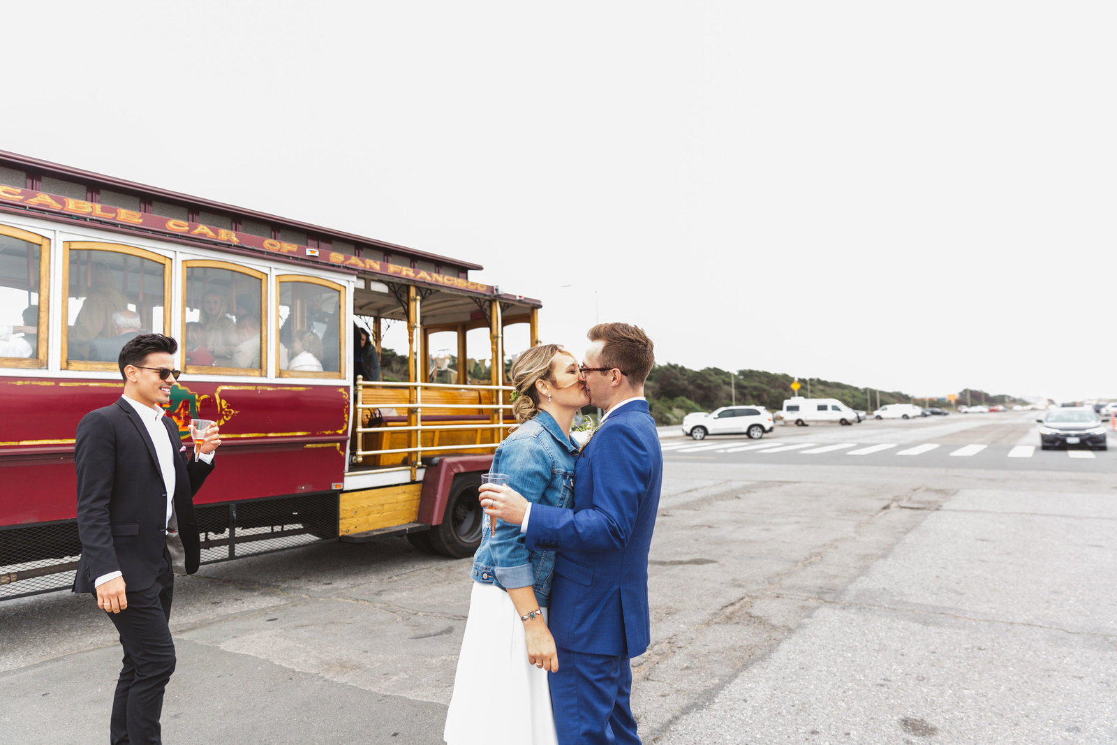 couple kissing while laughing with san francisco  streetcar trolley in the background