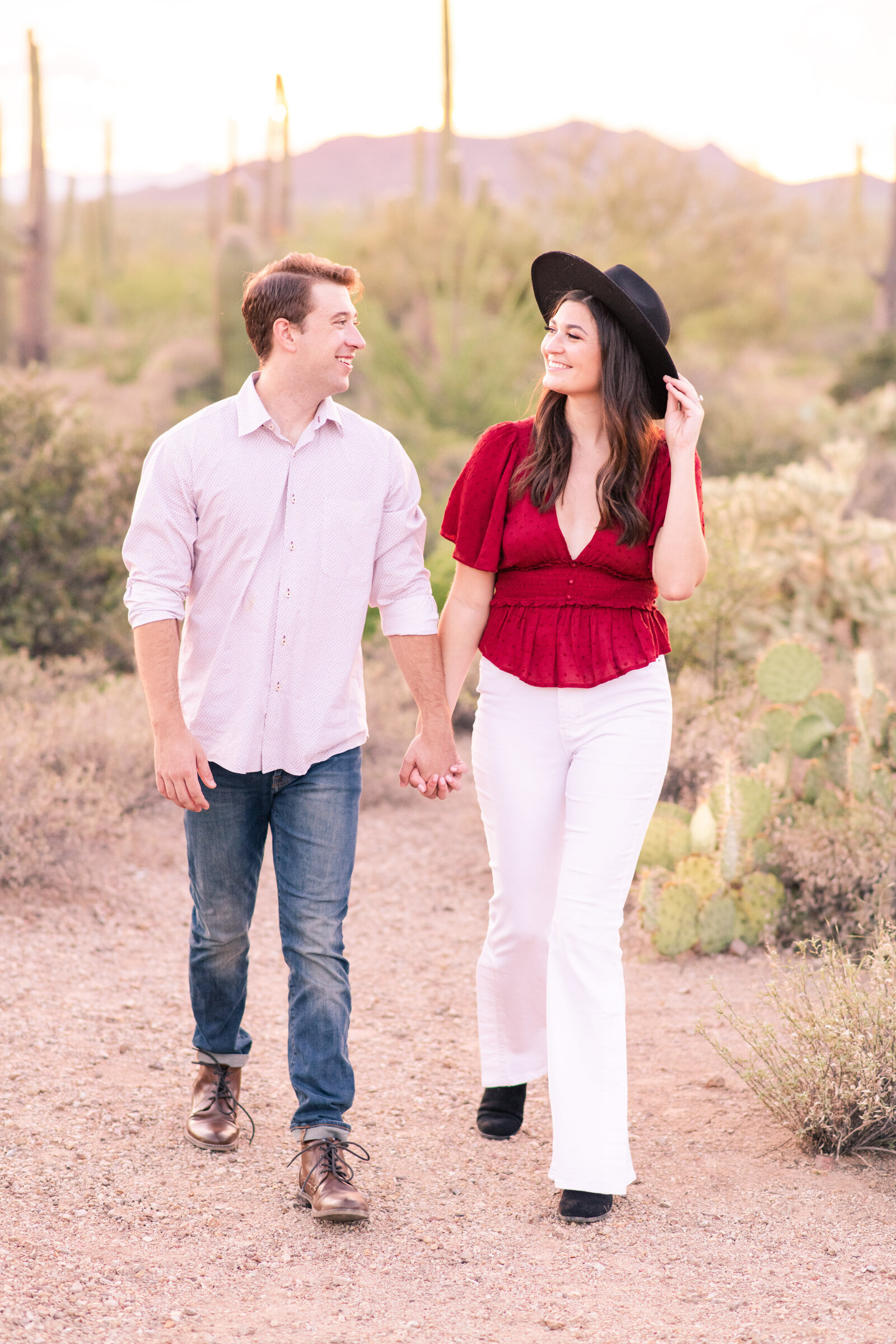 engaged couple walking in Tucson desert together and smiling