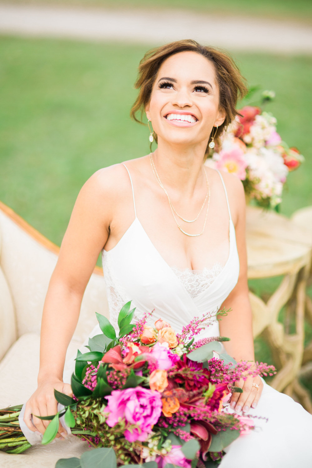 bride smiling while looking up and holding flowers