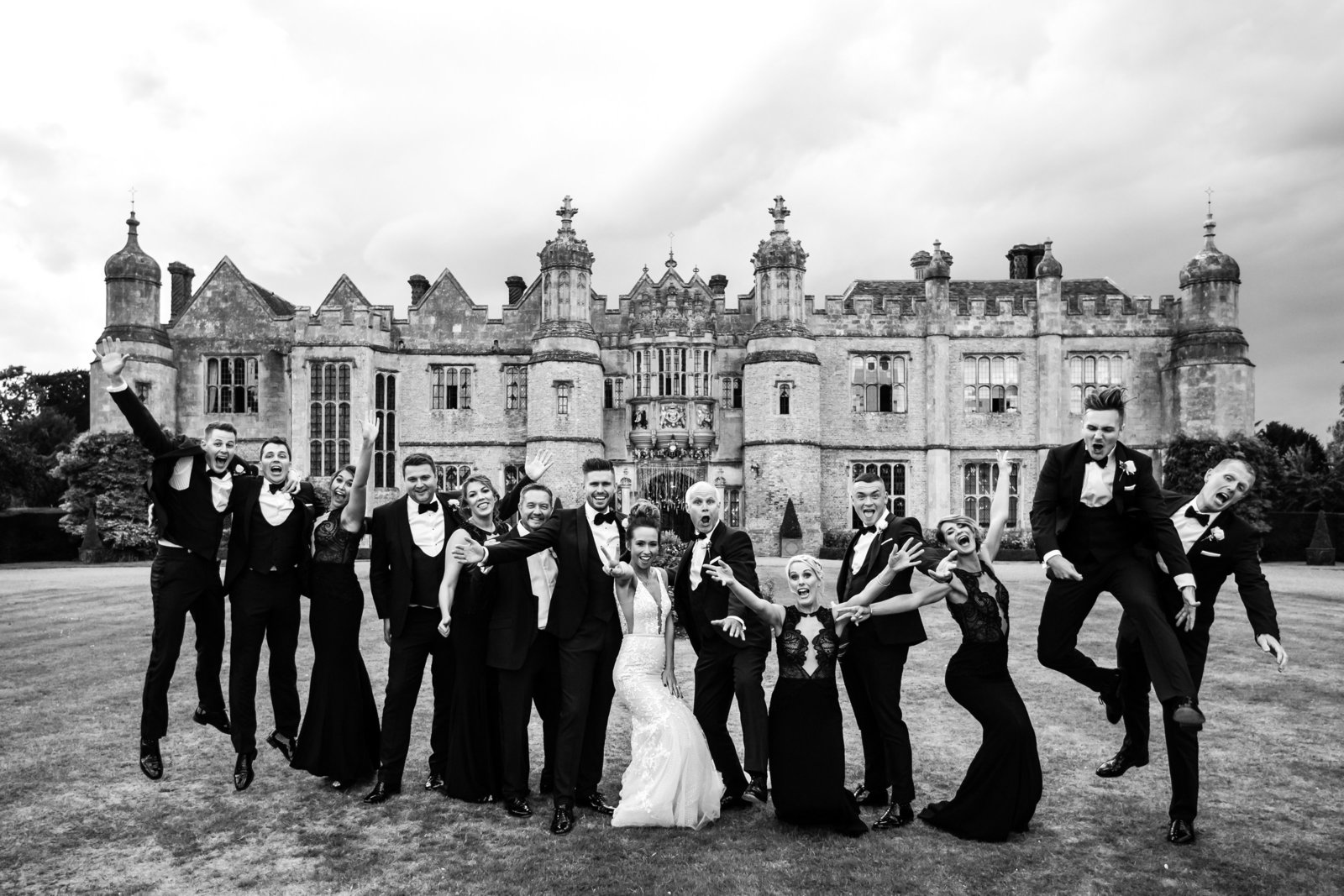 A wedding party jump for joy outside their Hengrave Hall wedding