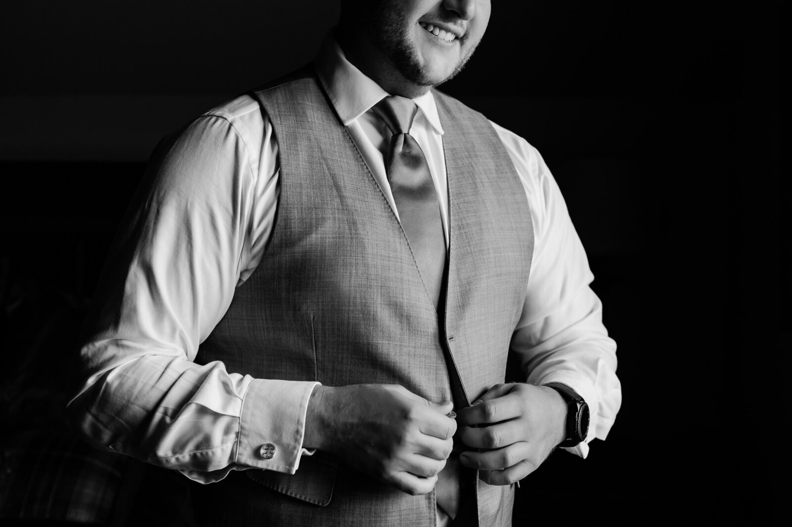 Black and white photo of a happy groom getting dressed for his Kansas City wedding
