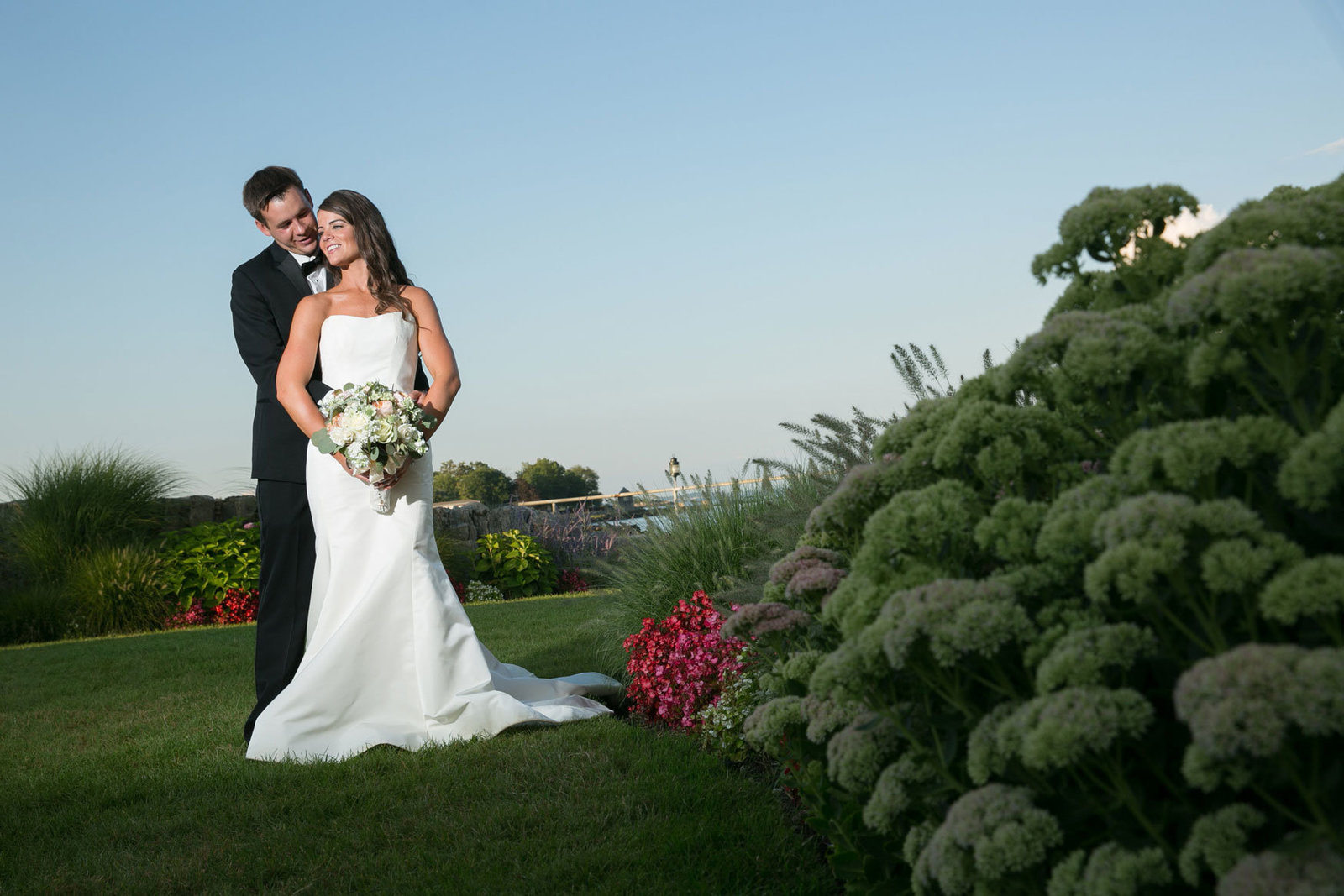 bride and groom posing outside Glen Island Harbor Club