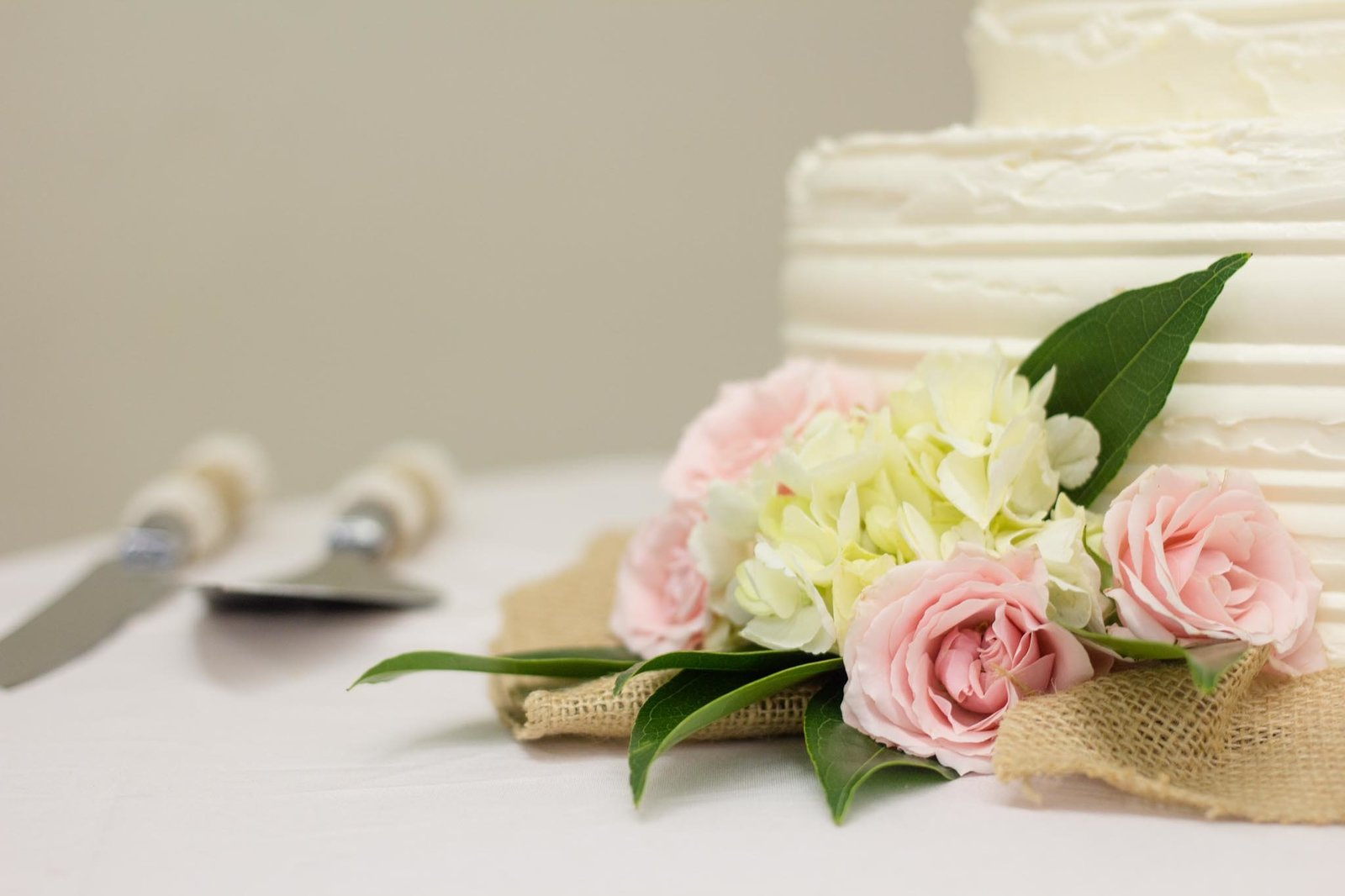 White wedding cake with blush, cream and green flowers on dessert table
