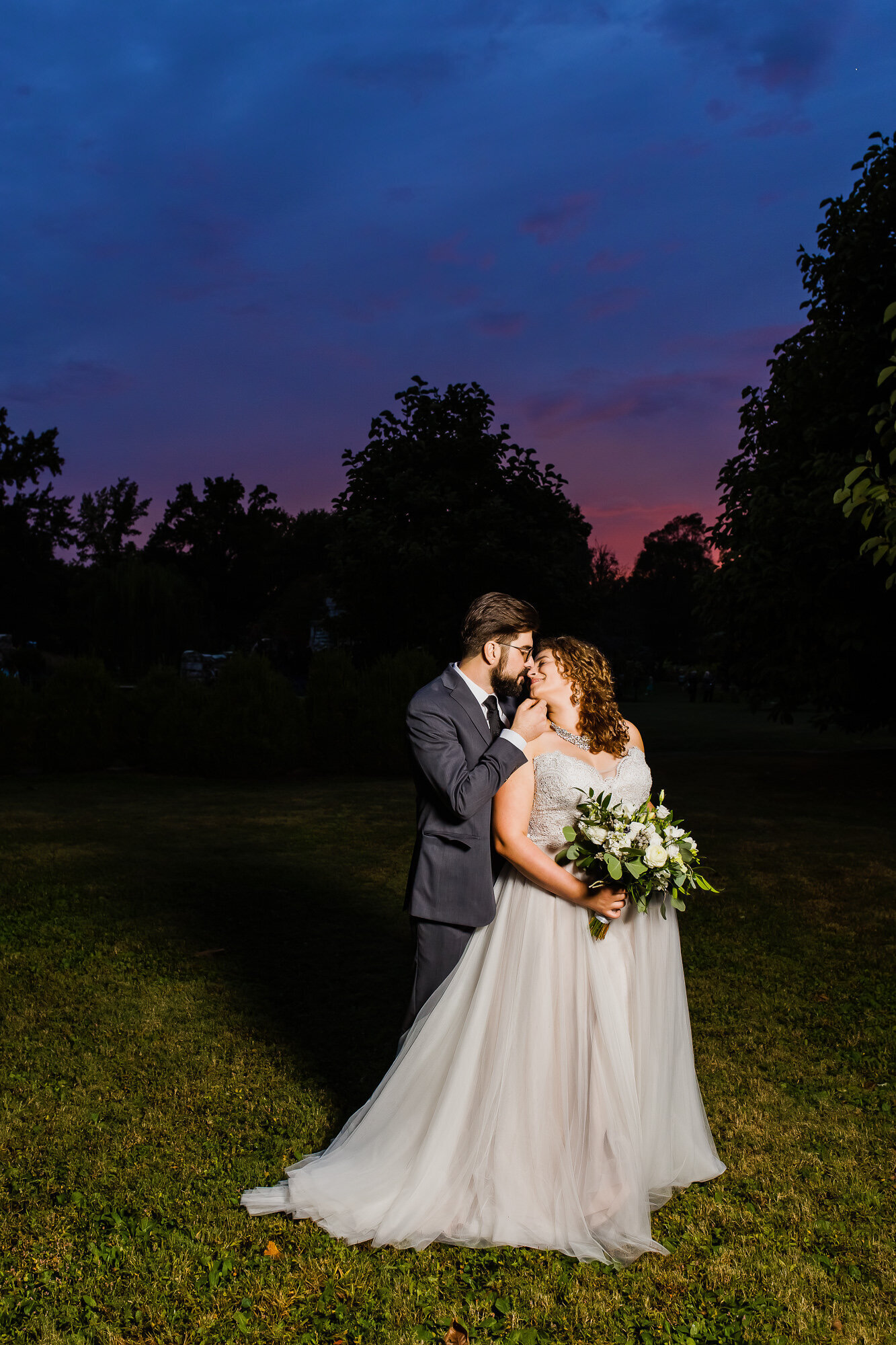 Bride and groom kissing at sunset in Tower Grove Park in St. Louis