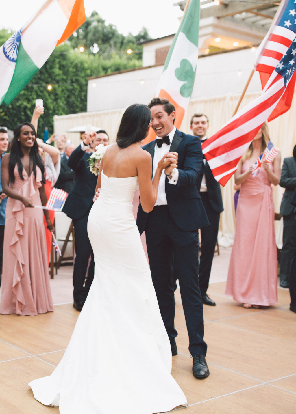 Bride and groom first dance during wedding reception with wedding party holding nationality flags at Butterfly Lane Estate in Montecito