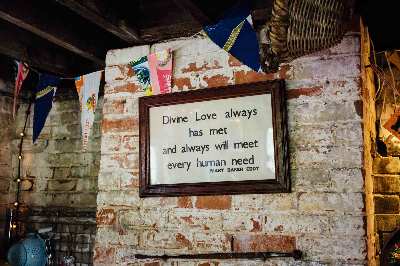Divine Love quote framed on the wall in the rustic barn at The Keeper and The Dell, Norfolk