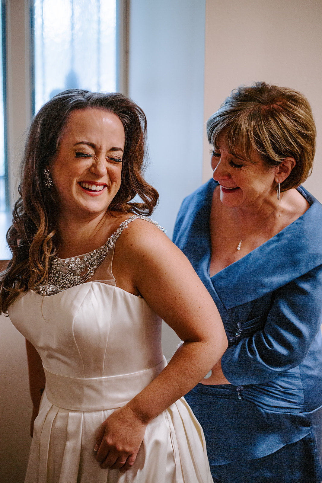 Mom helping her daughter put on her wedding dress during her Minneapolis Wedding day