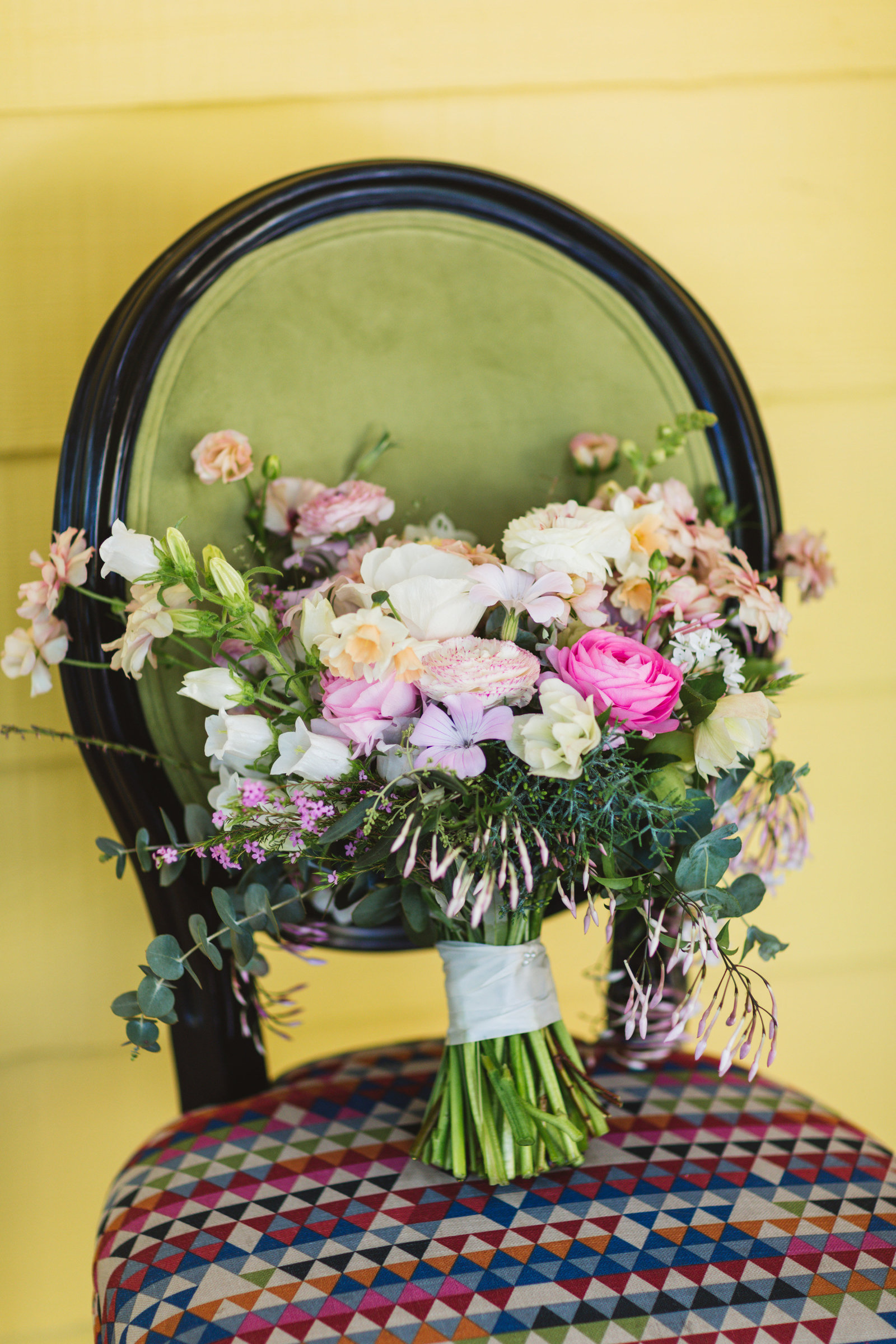 wedding bouquet by flowermama propped up on colorful chair at Vezer