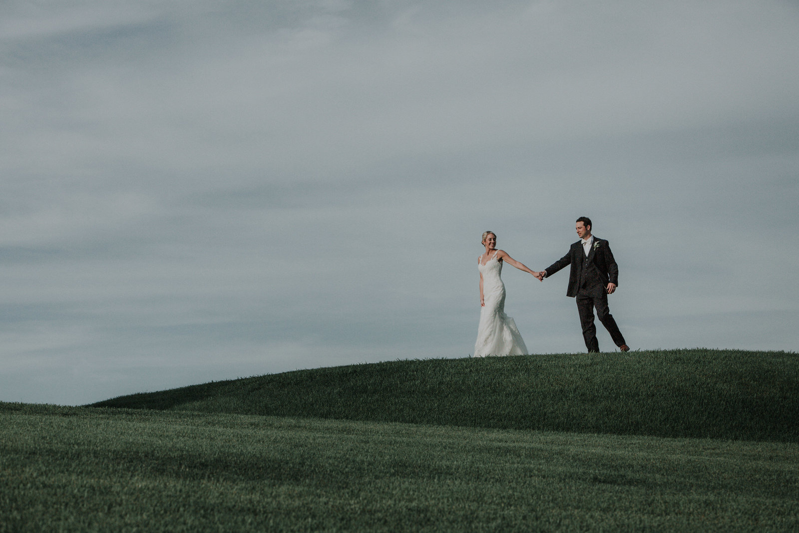 wedding couple walk along a grassy hill bridal gown by pronovias