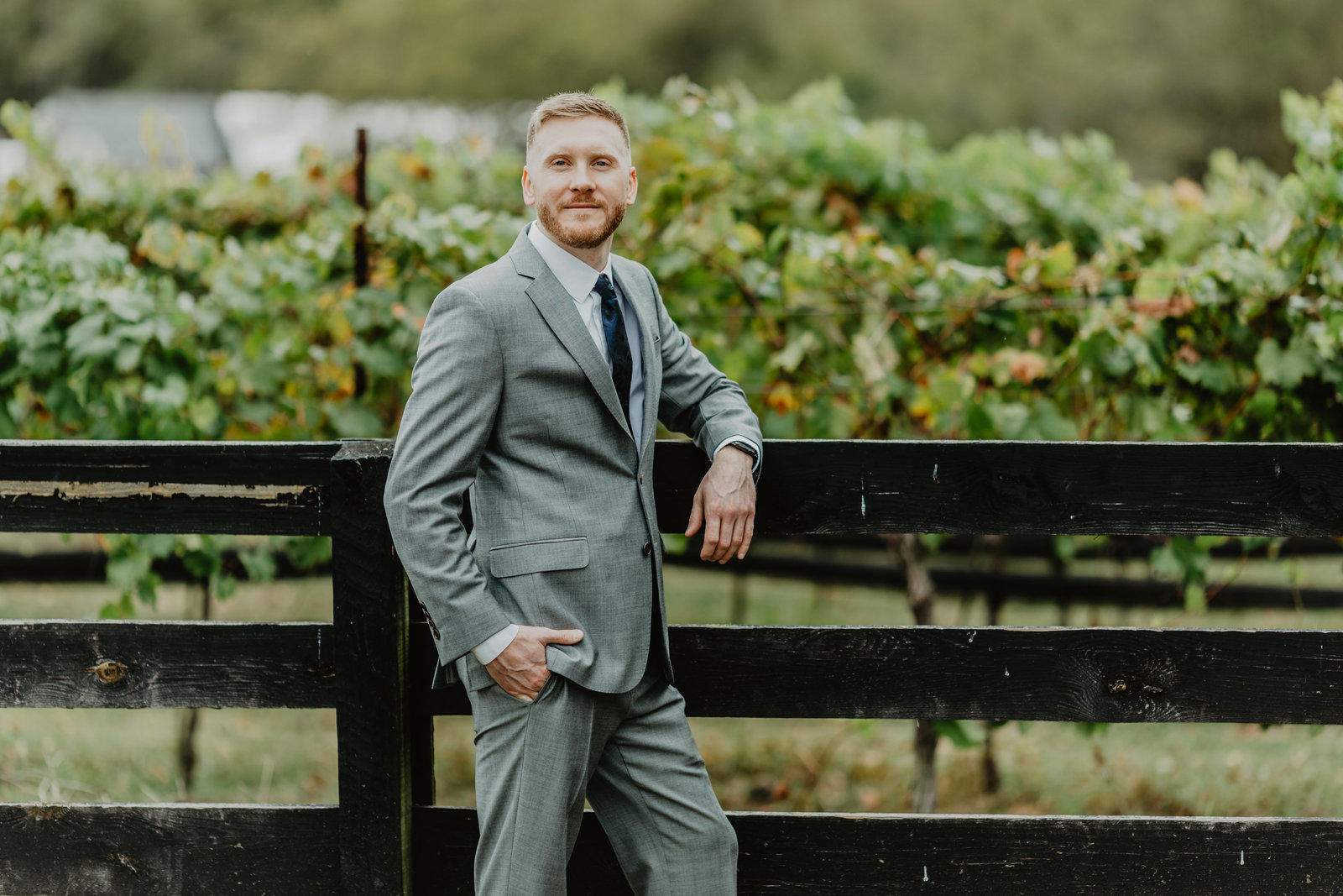 Groom leans on fence looking at the camera at Arrington Vineyards
