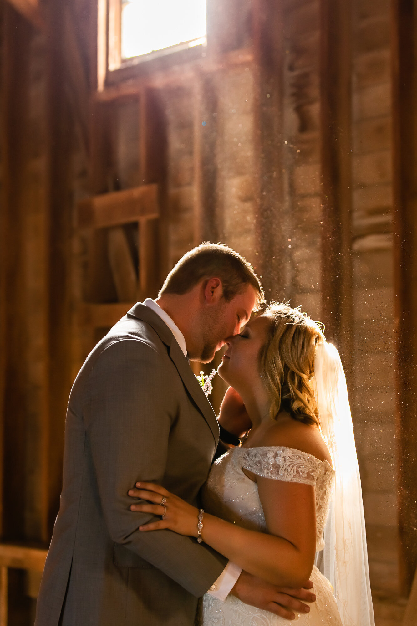 Romantic portrait of a bride and groom in a barn for their Kansas City wedding