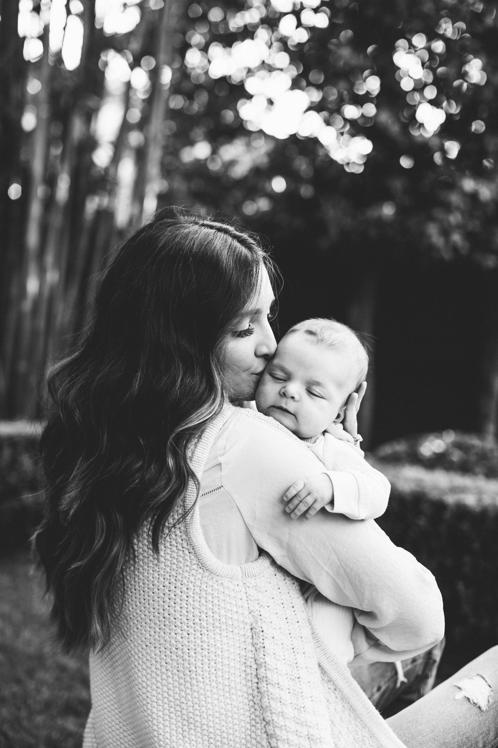 Classic black and white photo of mom kissing newborn