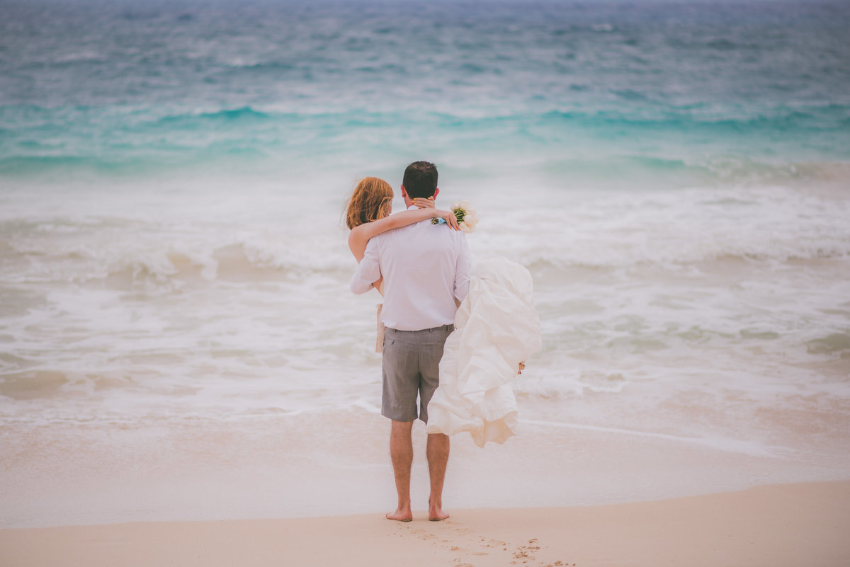 Groom holds bride while they look at the ocean in Hawaii.