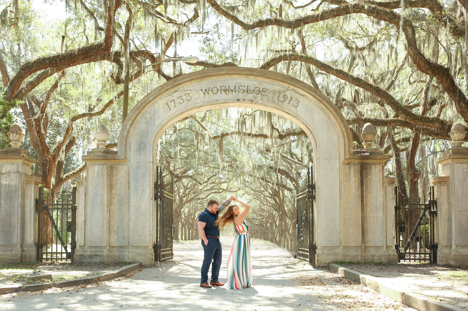 a couple twirling under the wormsloe plantation entrance