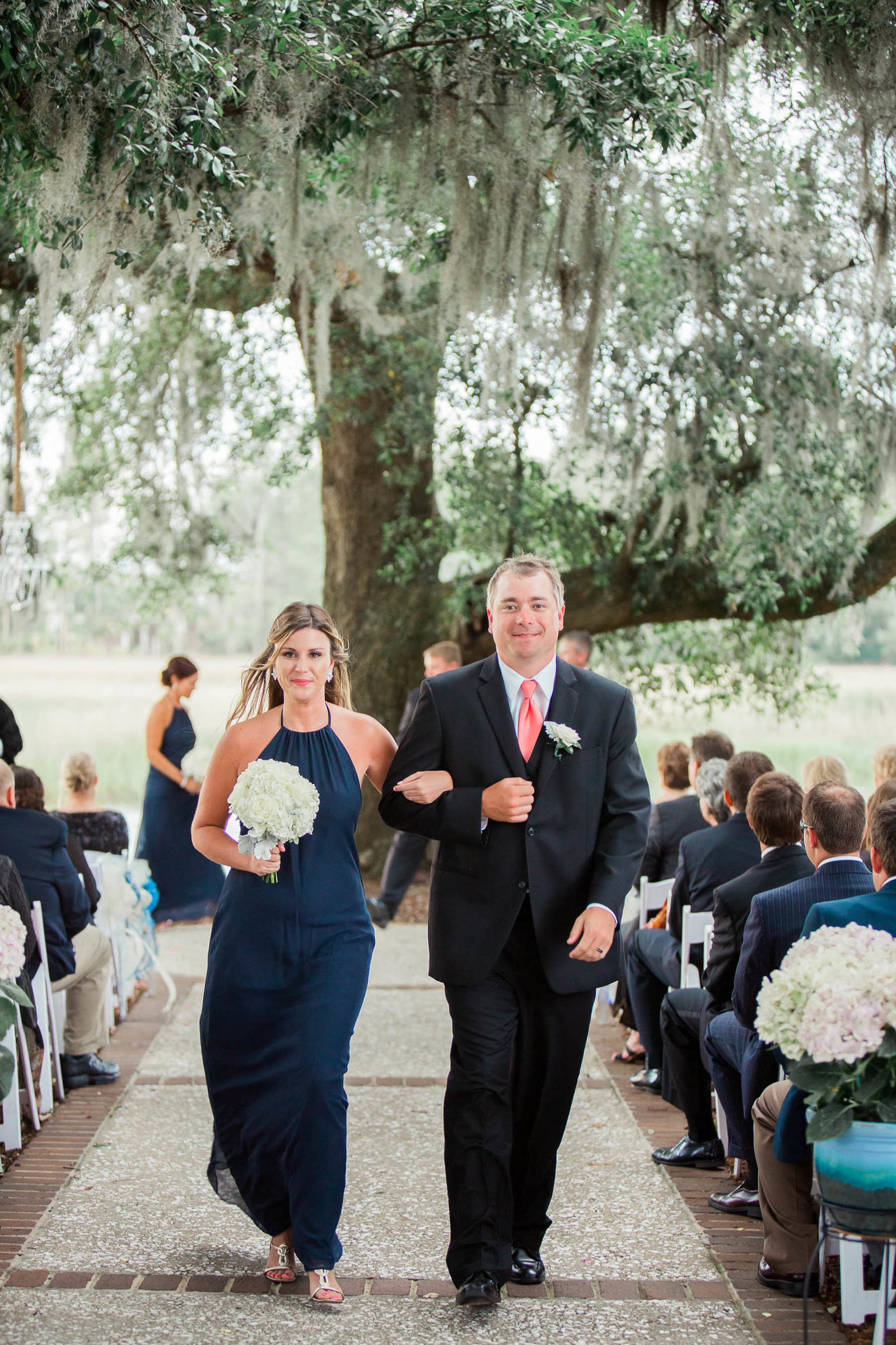 Bridesmaid and groomsman walk down the aisle, Dunes West Golf and River Club, Mt Pleasant, South Carolina